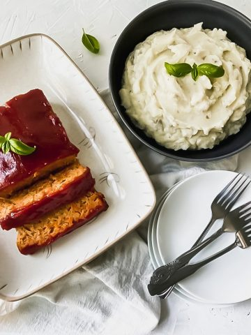 Healthy chicken meatloaf with hidden veggies on a serving platter with a side of mashed potatoes, plates, and forks.