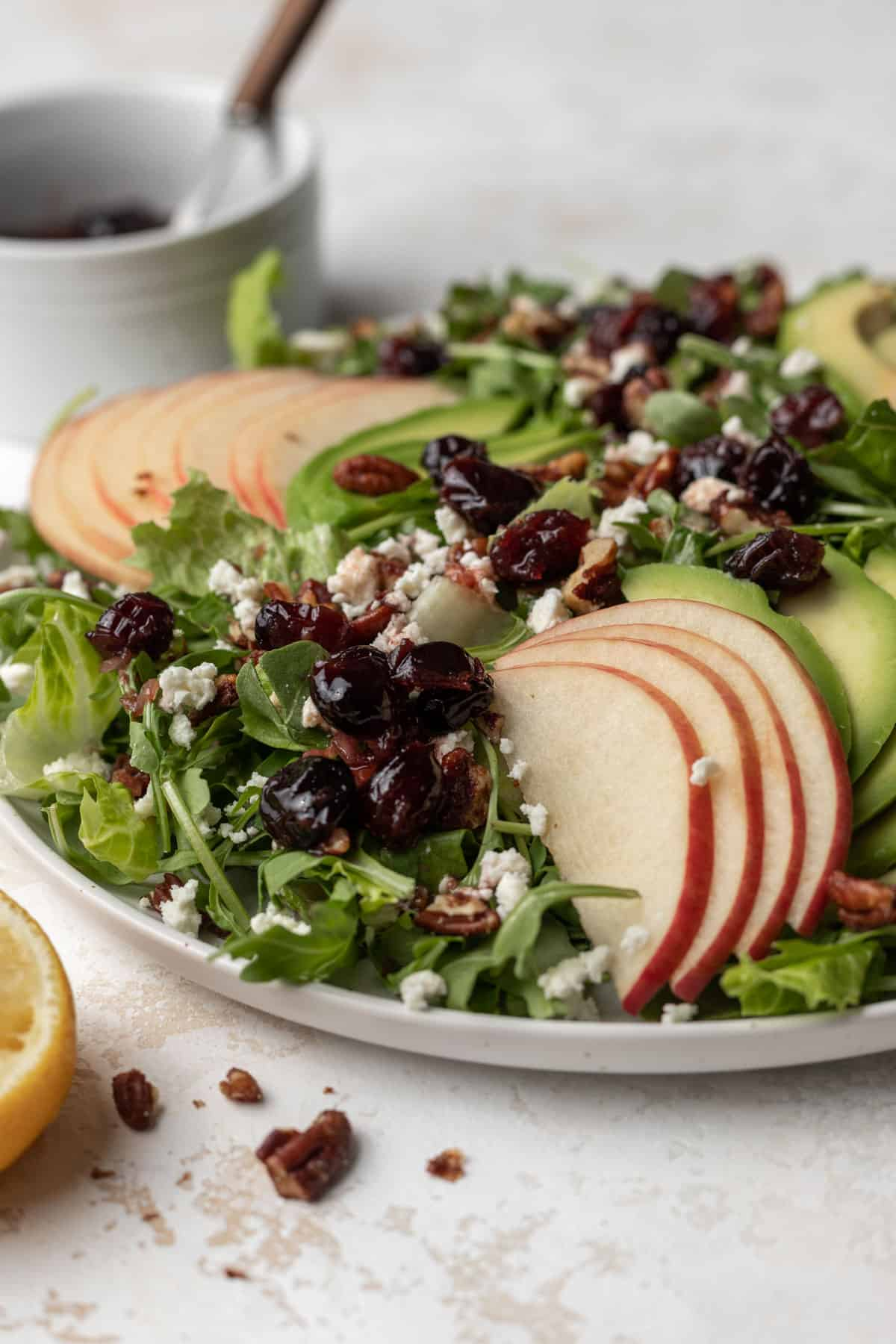 A side view of sliced apples on top of avocado and arugula salad topped with cranberry vinaigrette, toasted pecans, and feta.