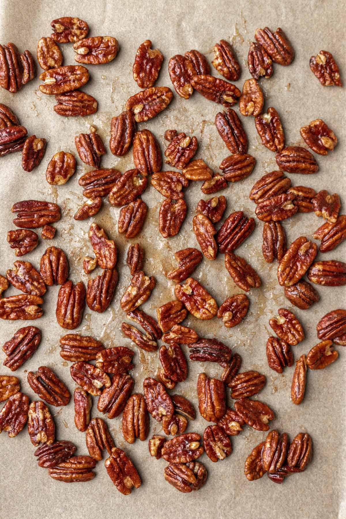 Maple cinnamon pecans on a sheet pan before toasting.