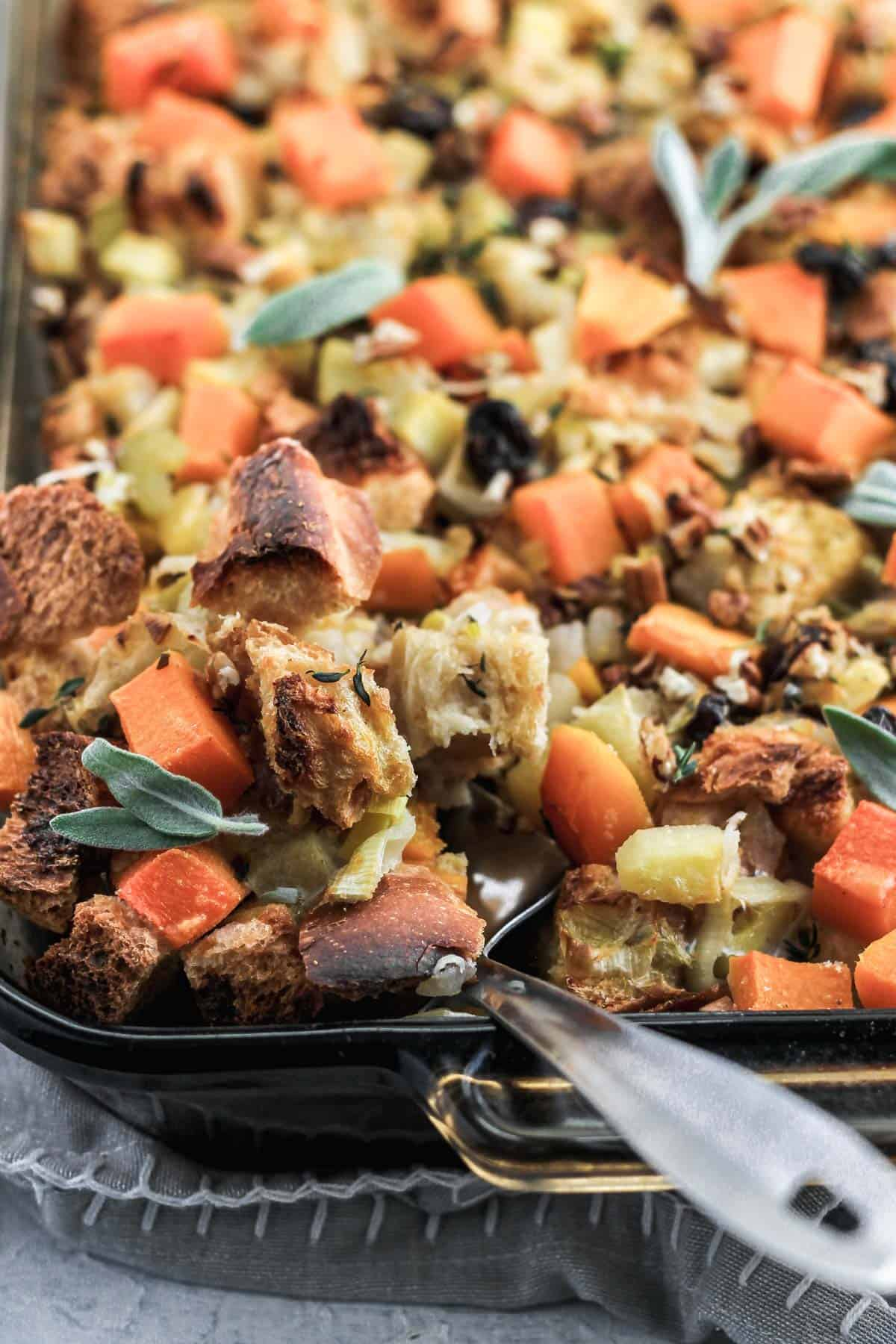 Butternut squash stuffing in a glass dish with a metal spatula scooping out some stuffing.