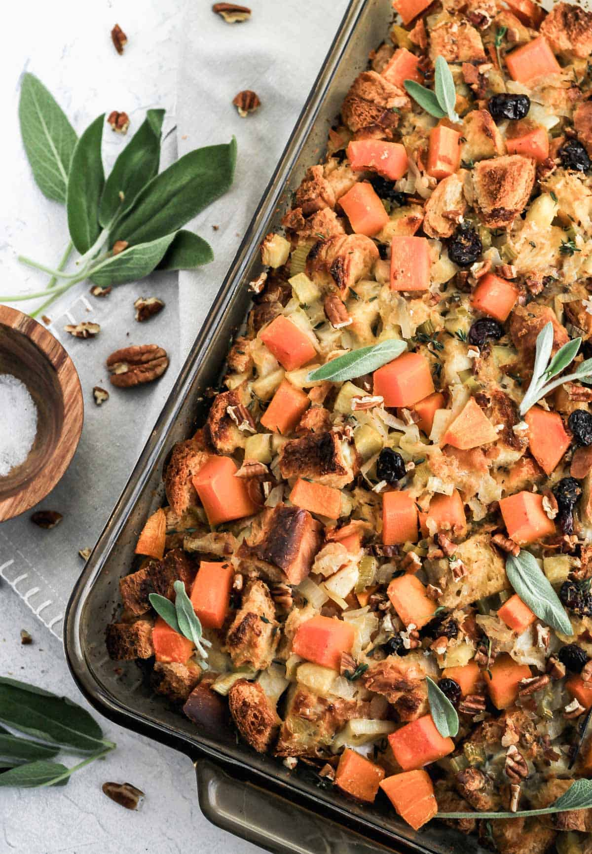 Butternut squash stuffing in a glass dish with a wooden bowl filled with salt and sage leaves on the side.