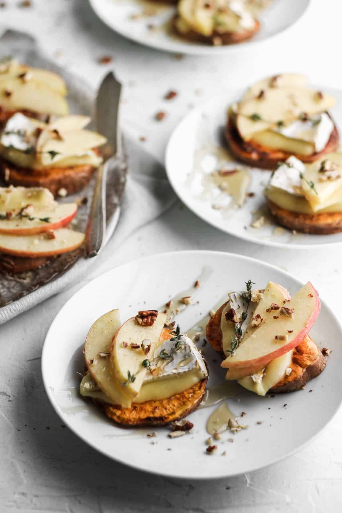 2 apple and brie sweet potato crostini on small white appetizer plates.