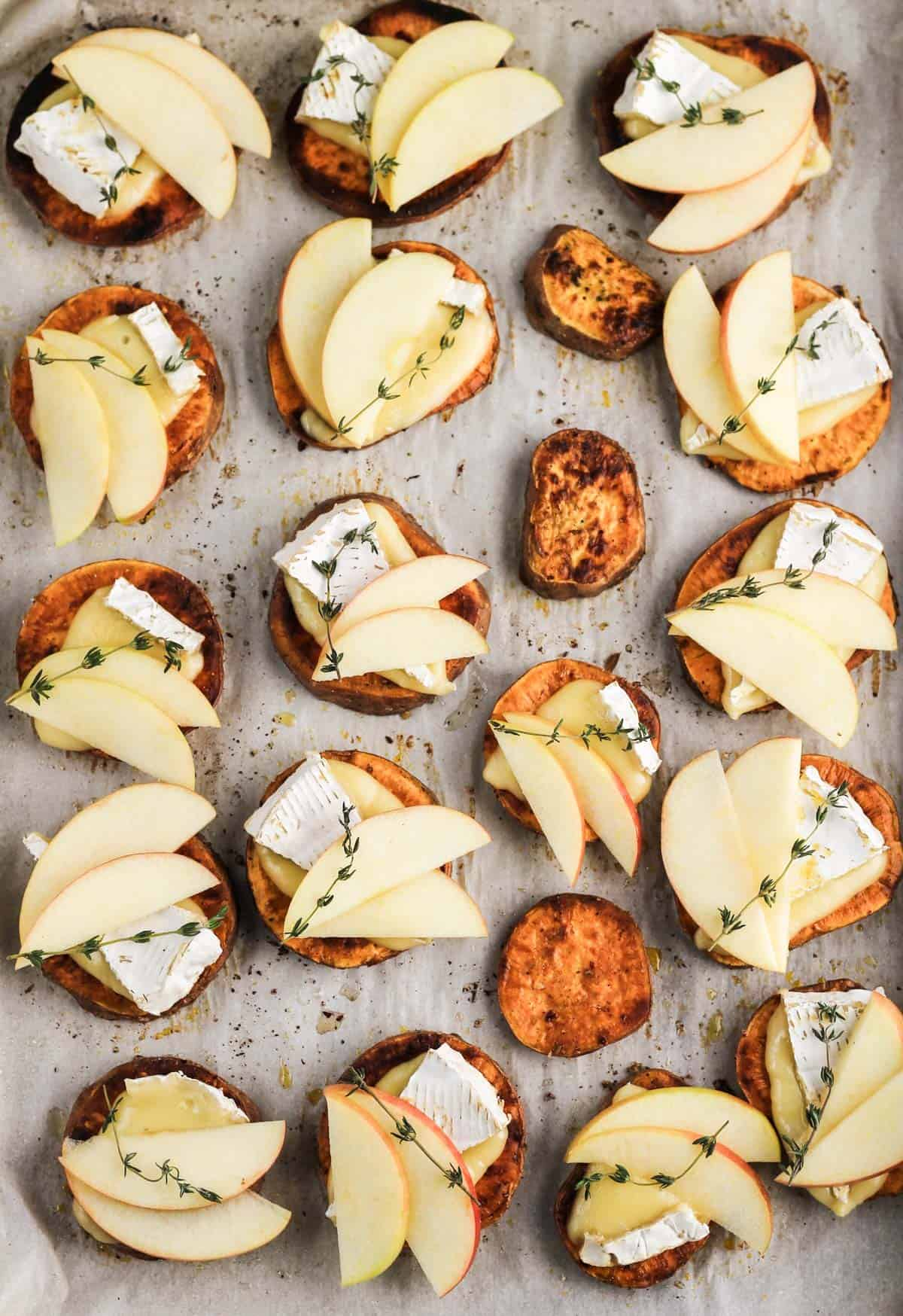 Assembled apple and brie sweet potato crostini on a parchment-lined sheet pan.