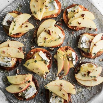 Apple and brie sweet potato crostini on a glass plate with a grey napkin underneath.