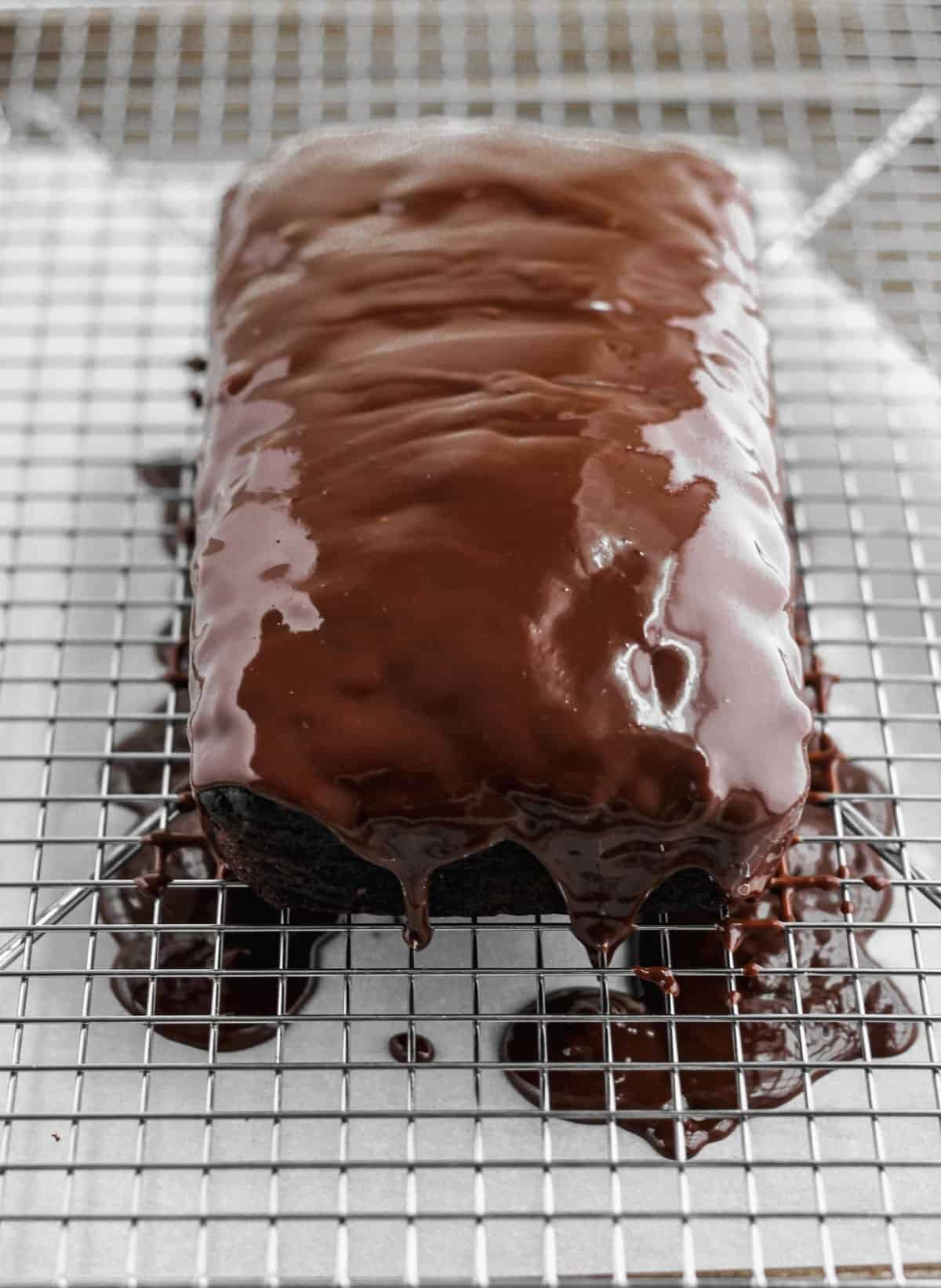 Chocolate glaze poured over the chocolate zucchini bread on top of a wire cooling rack.