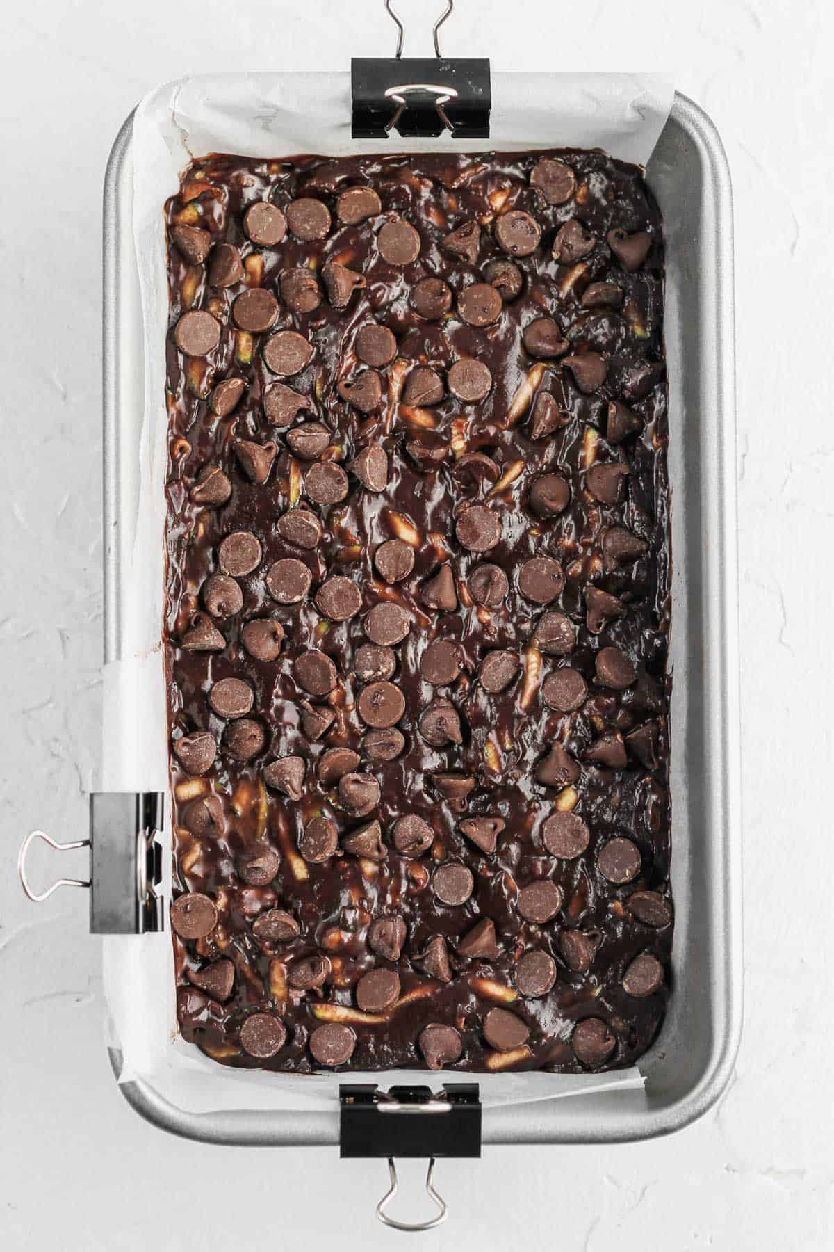 Raw death by chocolate zucchini bread batter topped with chocolate chips in a loaf pan.
