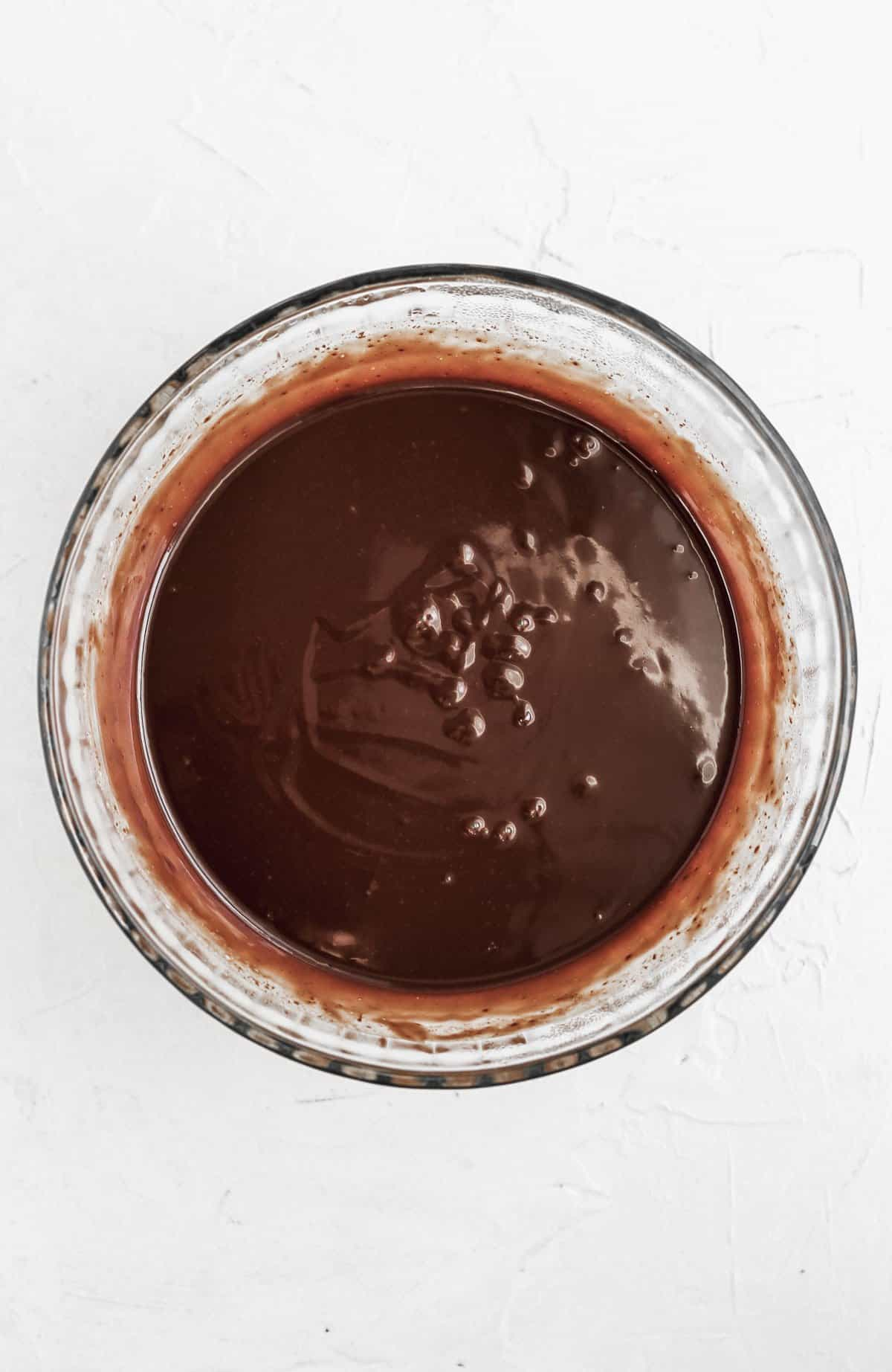Smooth and shiny chocolate ganache in a glass bowl.