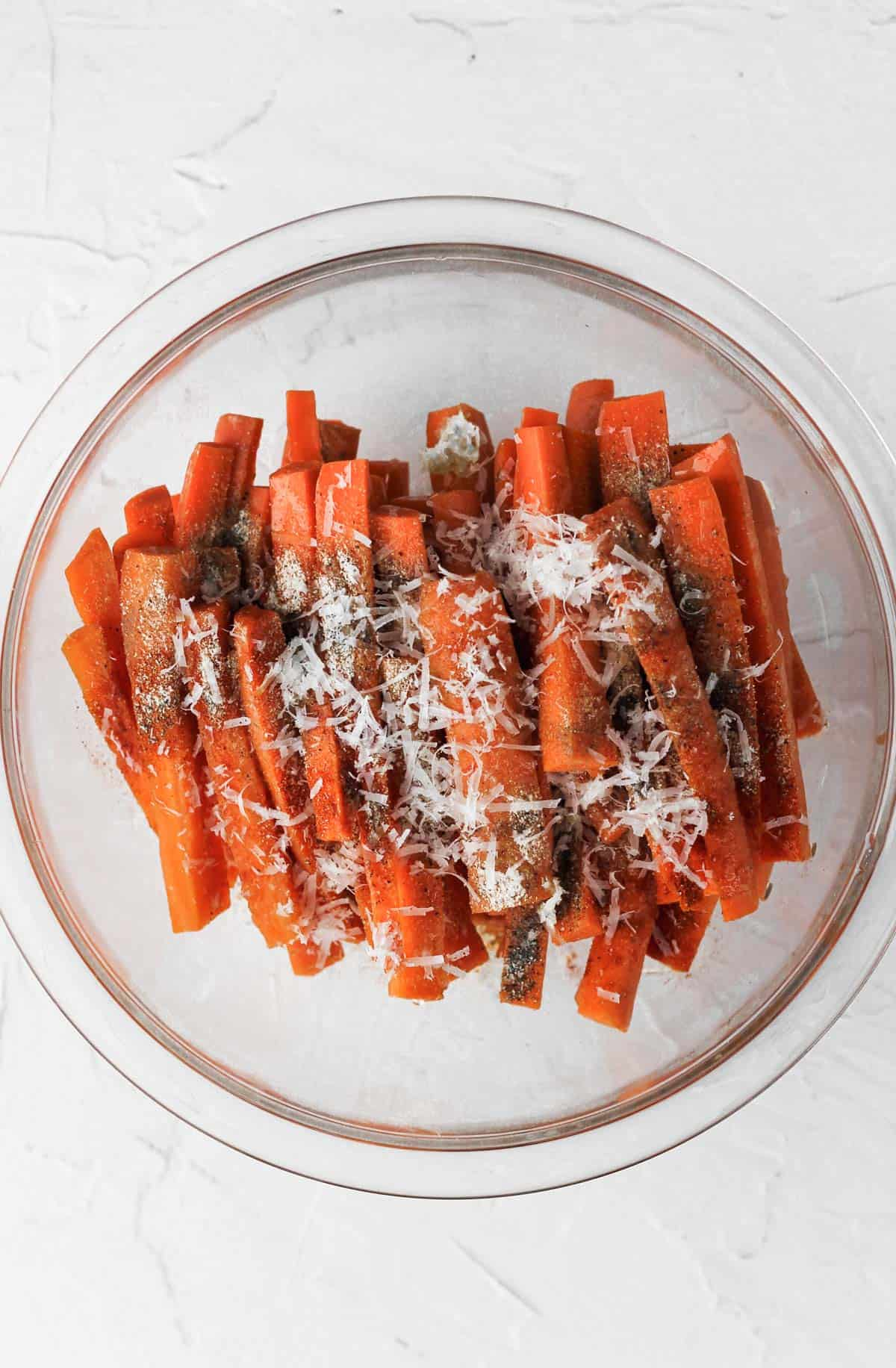 Cut carrots in a glass bowl topped with seasonings.