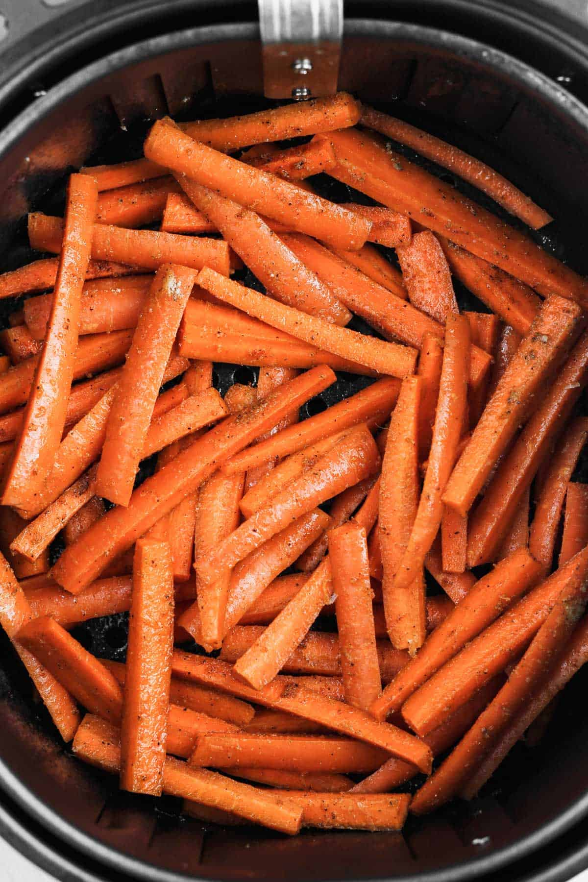 Cut and seasoned carrots in an air fryer basket.