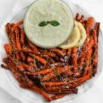 Air fryer carrot fries in a white bowl, garnished with freshly grated parmesan cheese, lemon slices, and a bowl of pesto aioli on the side.