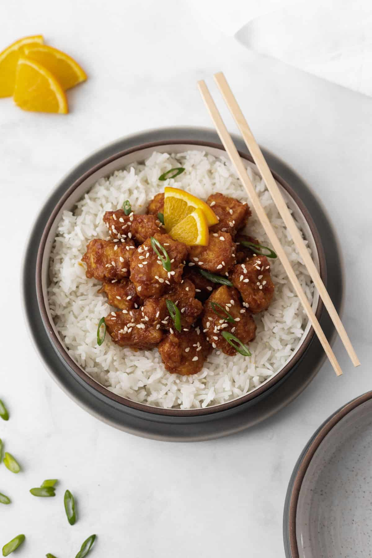 Air fryer orange chicken on top of white rice in a gray bowl with green onions and orange slices around it.
