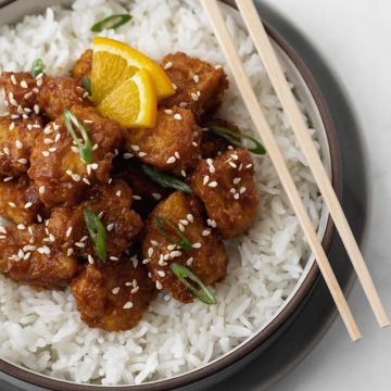 Close up of air fryer orange chicken on top of white rice in a gray bowl.