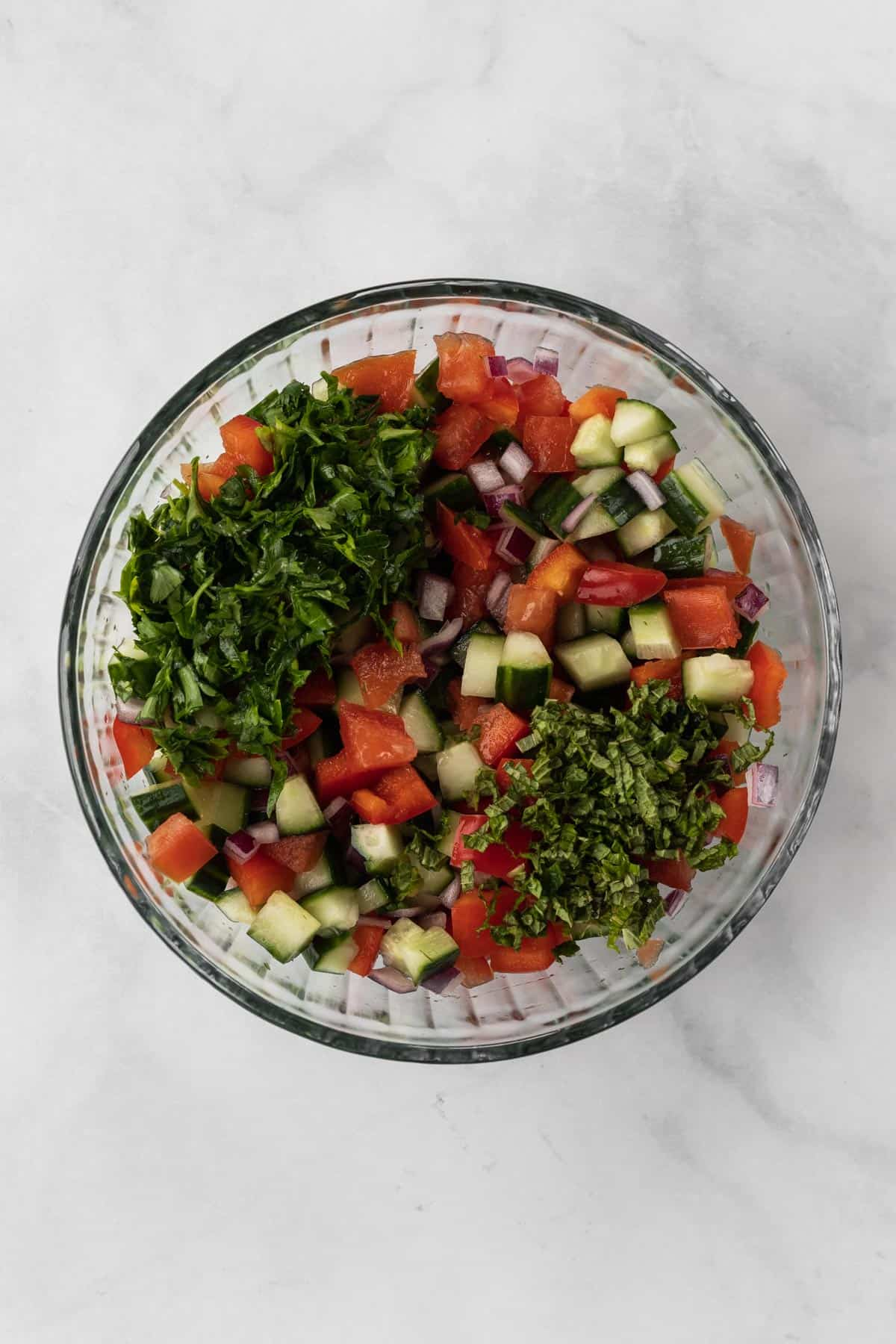 All of the ingredients for israeli salad in a glass bowl.