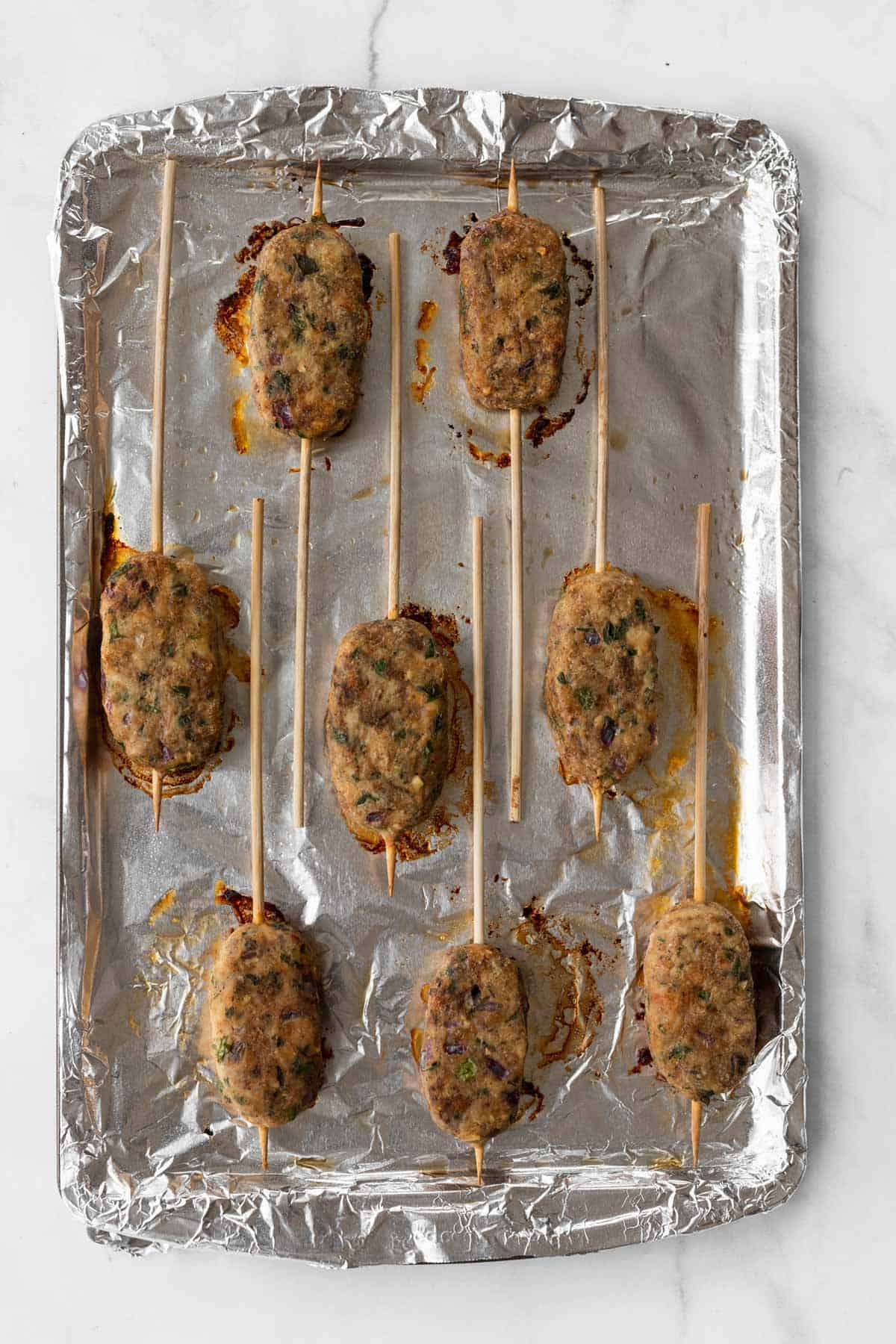 Cooked chicken kofta kebabs on a foil-lined sheet pan.