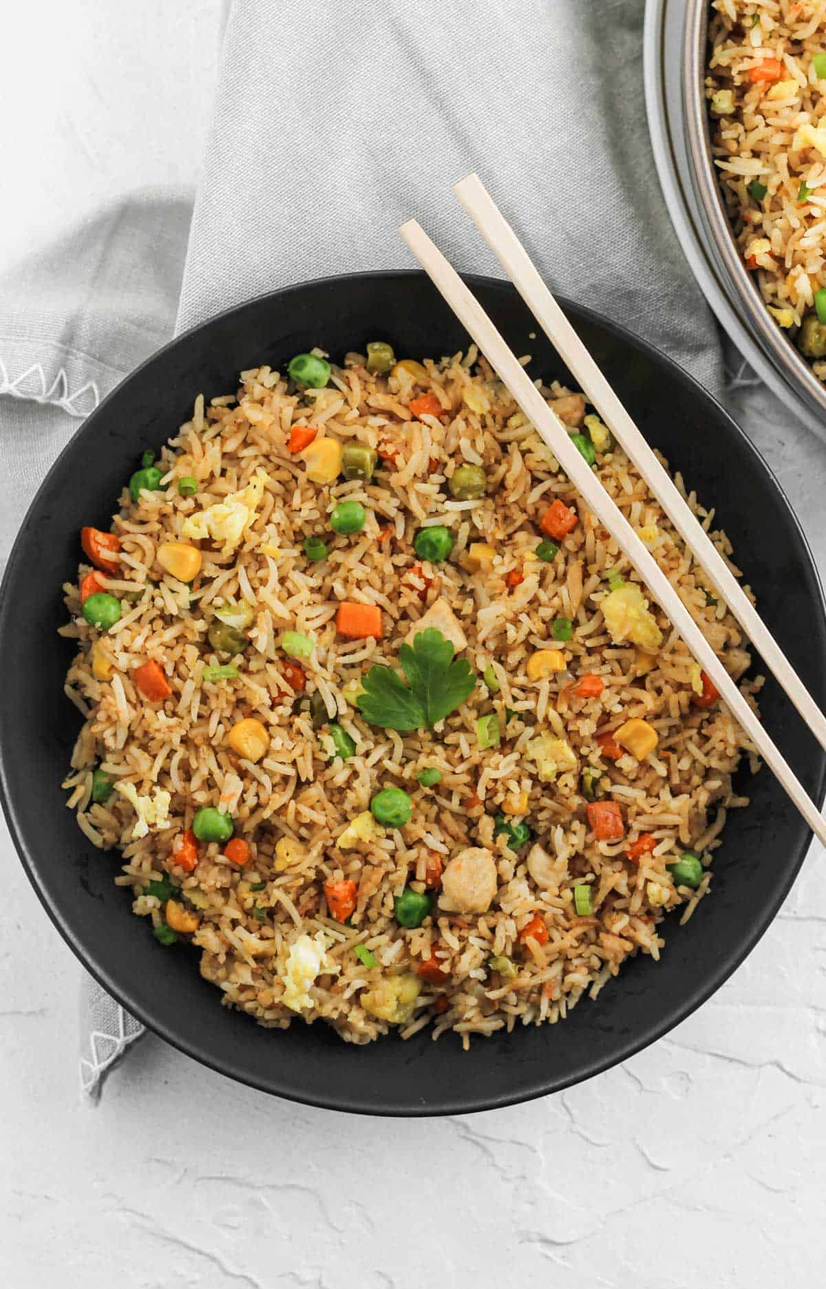 Chicken fried rice in a black bowl with chopsticks across the top.