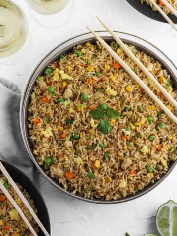 Instant pot chicken fried rice in a gray bowl with chopsticks on top and a glass of white wine to the top left.