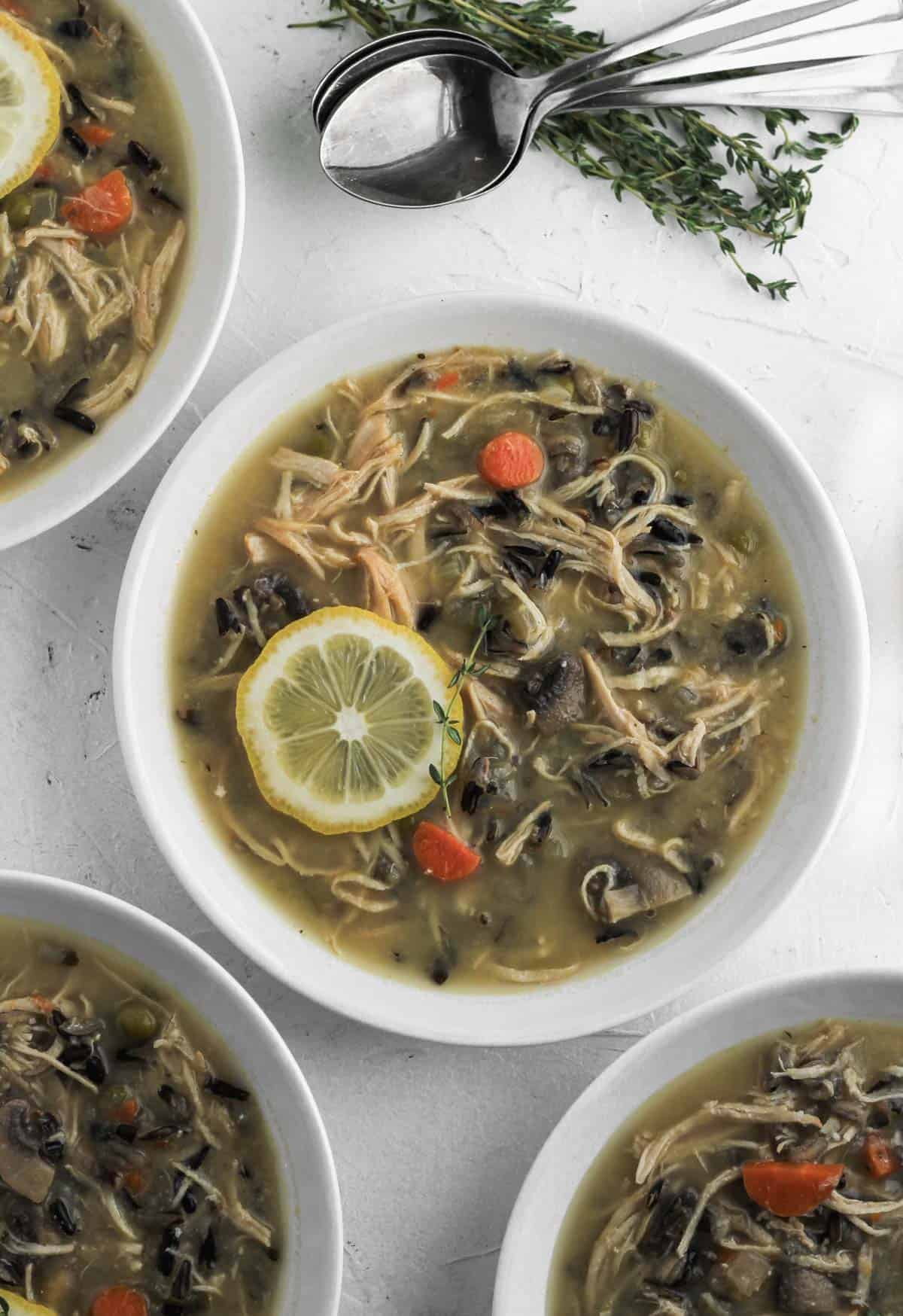 Instant pot chicken soup in 4 white bowls with spoons and sprigs of thyme to their top right.