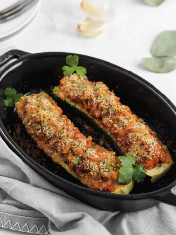 Italian zucchini garnished with parsley in a black baking dish.