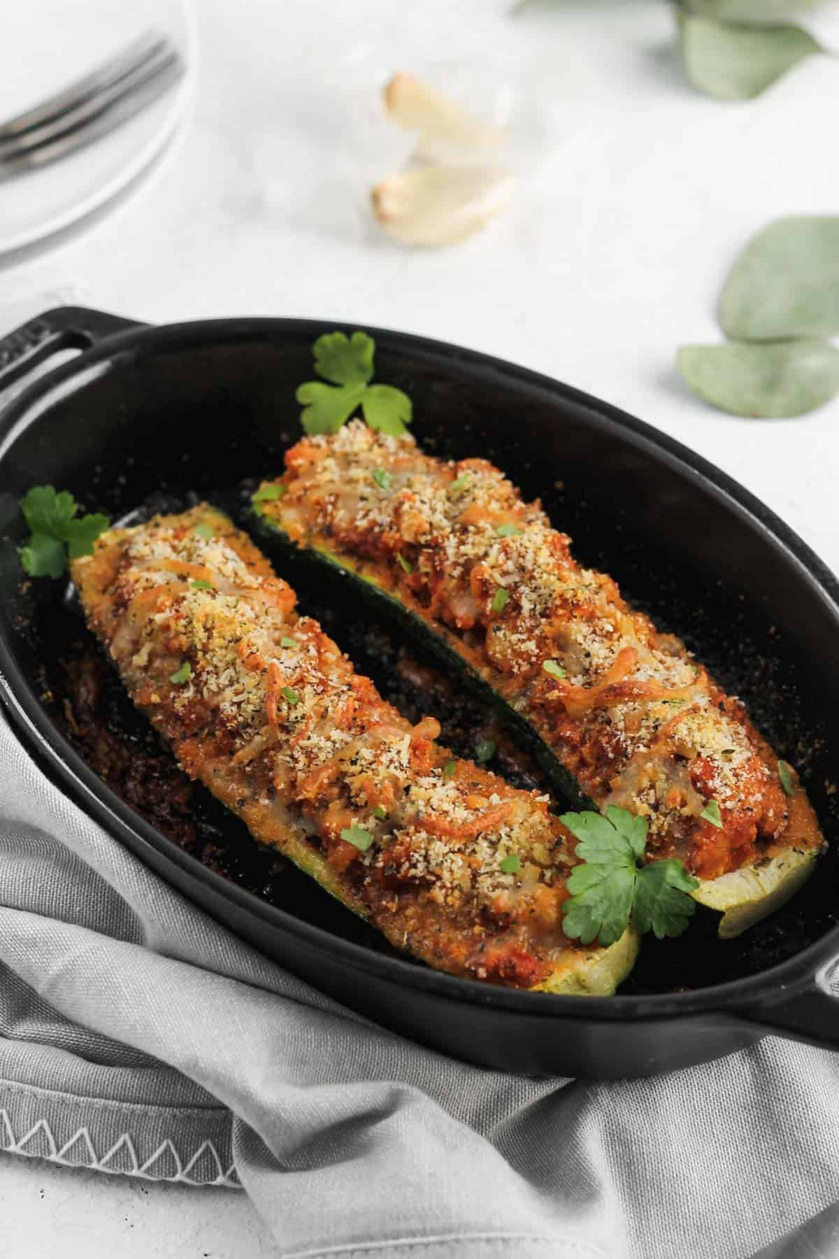 Stuffed zucchini boats garnished with parsley in a black baking dish.