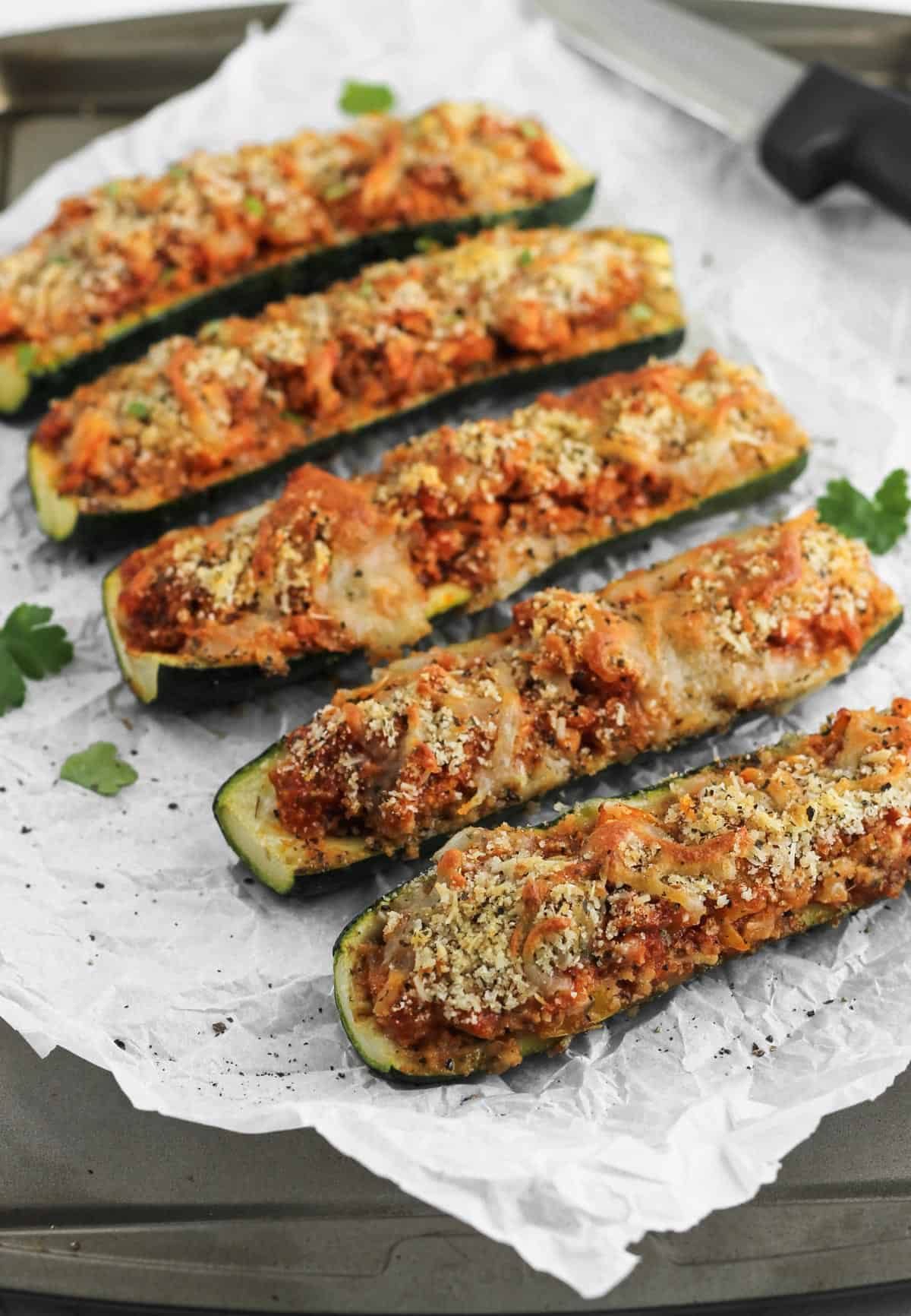 Italian zucchini arranged on a baking tray layered with parchment paper and parsley garnish.