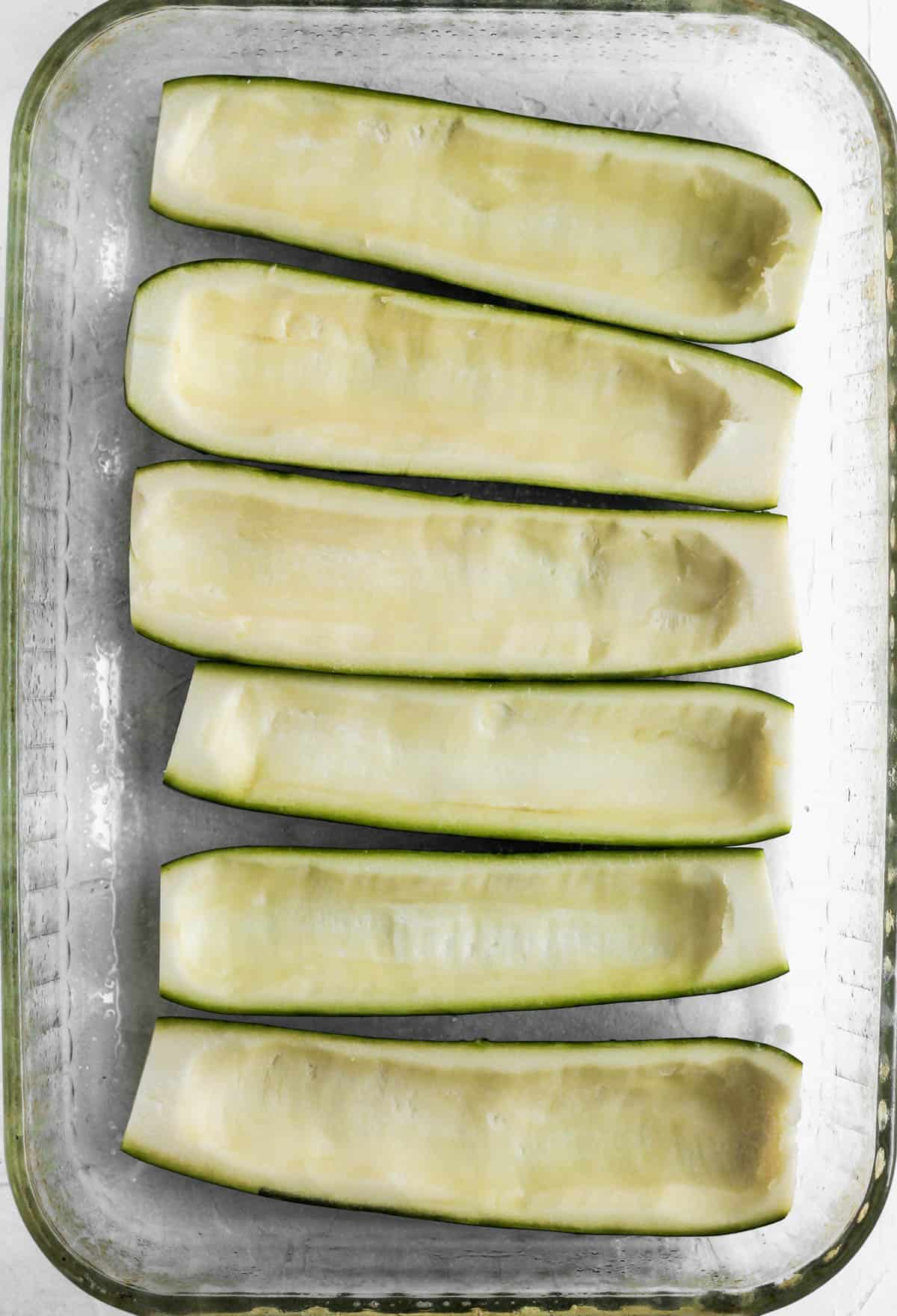 6 hollowed out zucchini halves in a glass baking dish.
