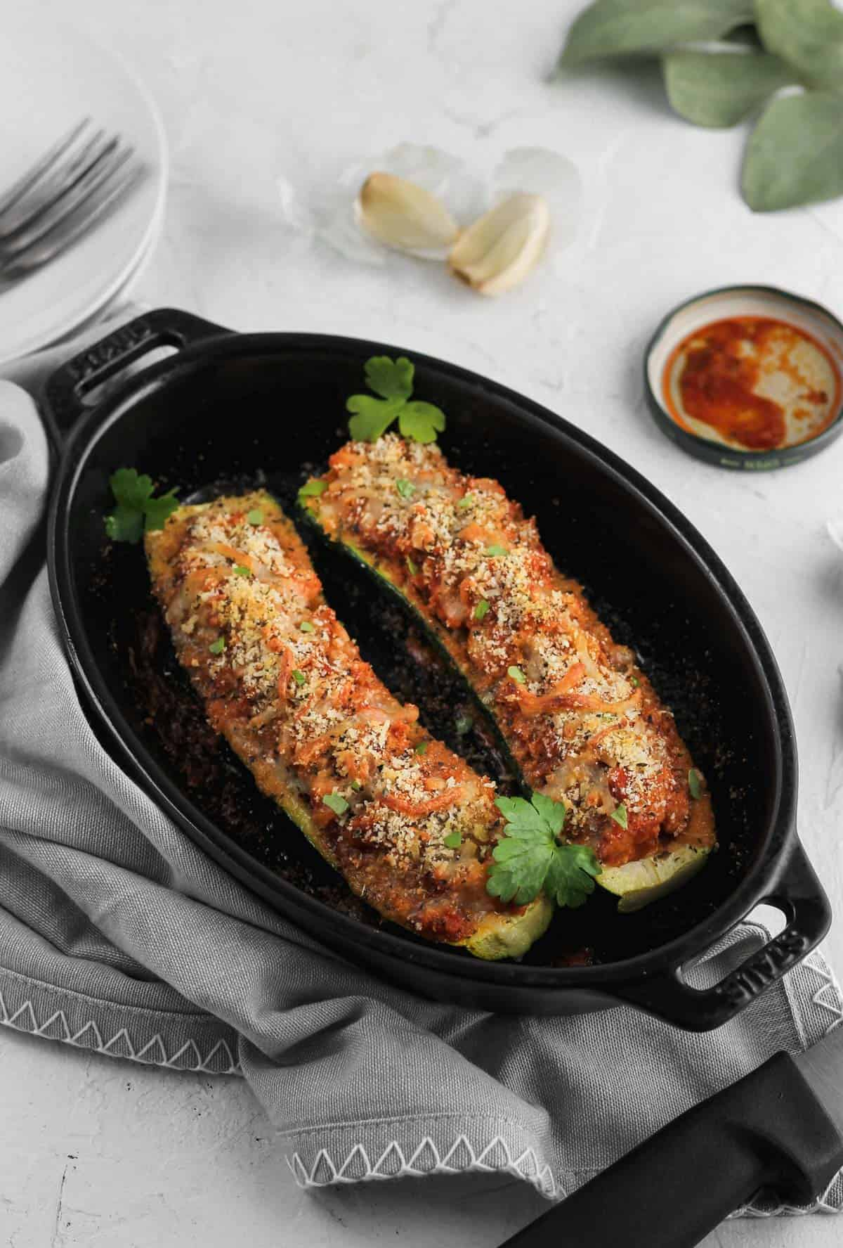 Stuffed zucchini in a black baking dish with a gray napkin and garlic cloves off to the side.