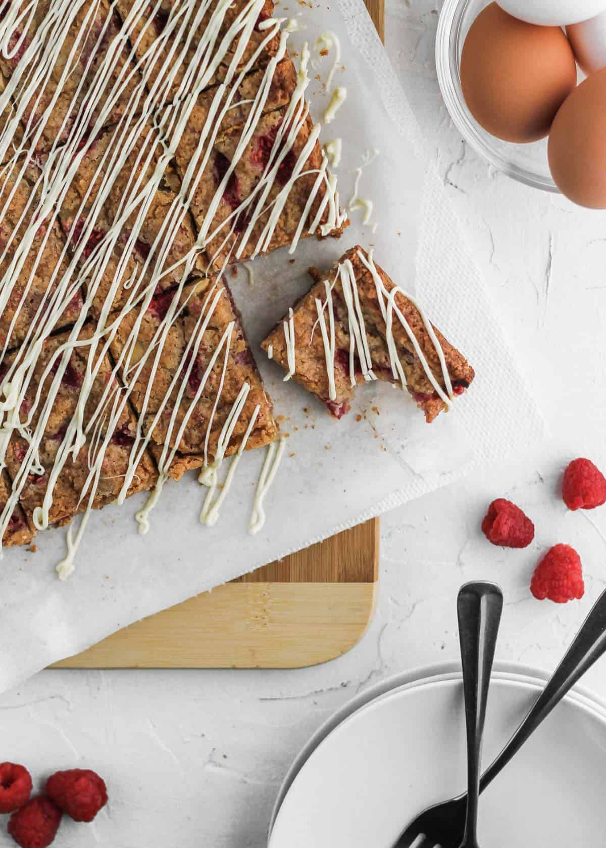 Blondie bars drizzled in white chocolate with a bite taken out on top of a wooden cutting board and with raspberries on the side.