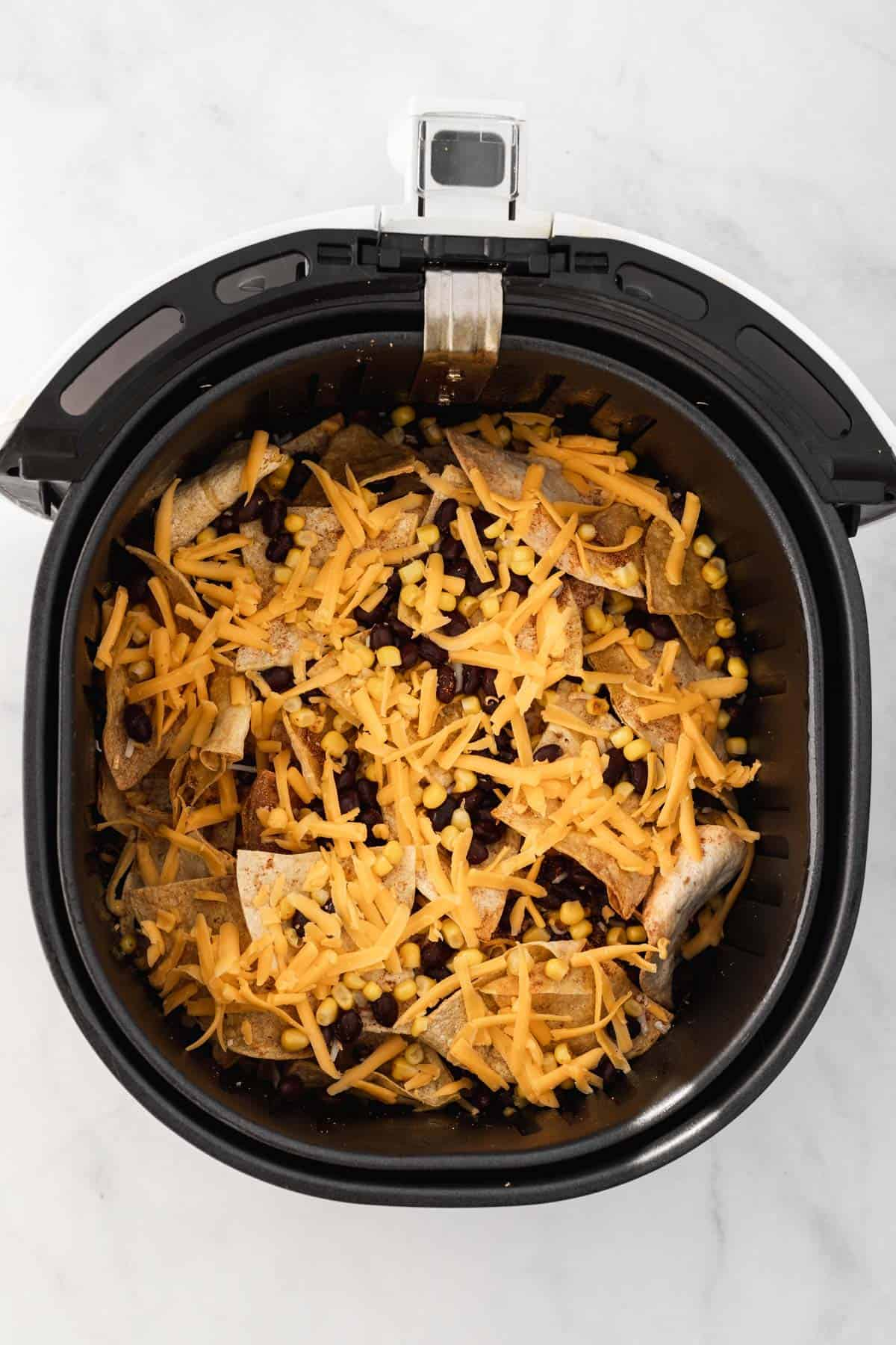 Tortilla chips, black beans, corn, and cheese layered in an air fryer basket.
