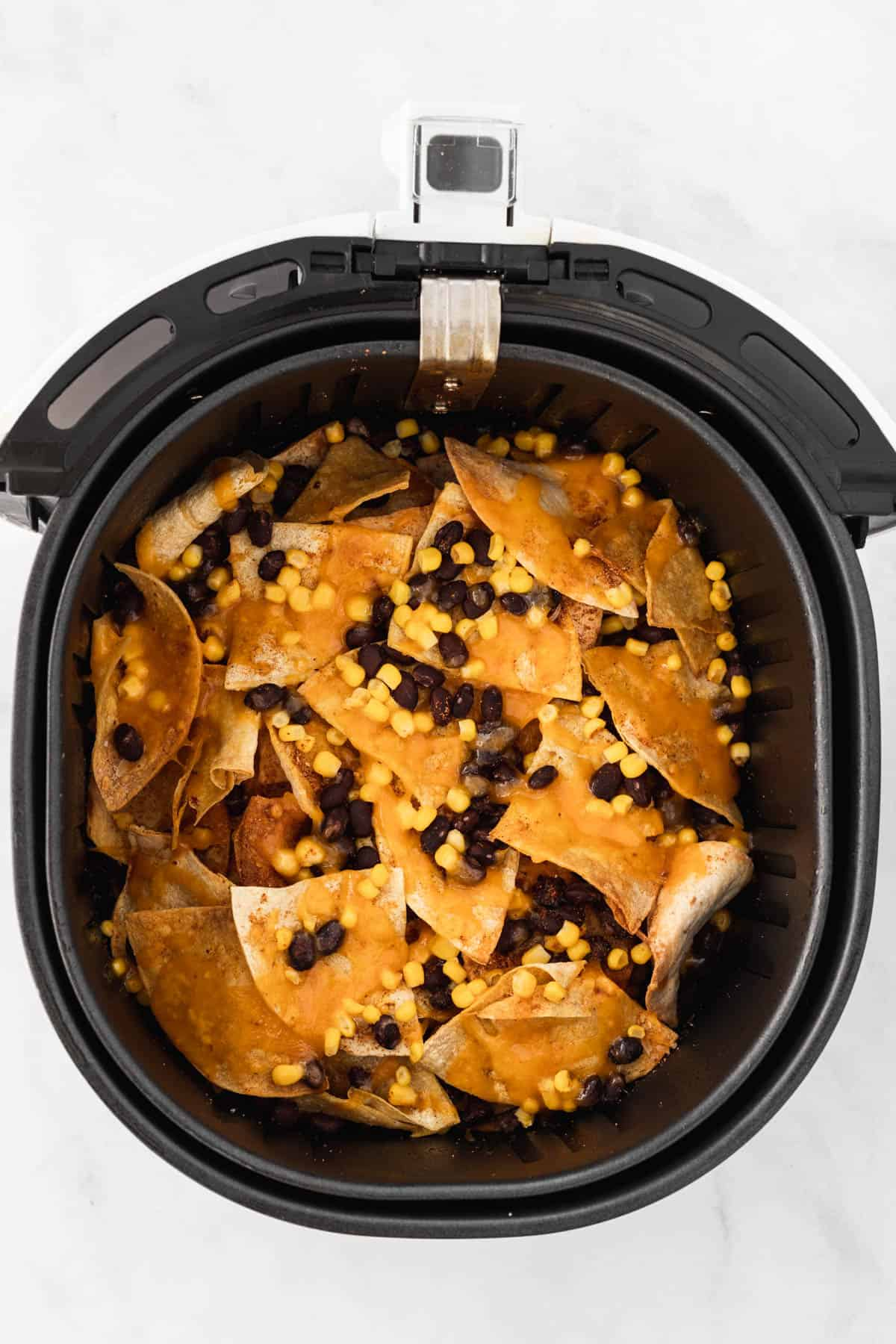 Melted cheese on top of layered tortilla chips, black beans, and corn in an air fryer basket.