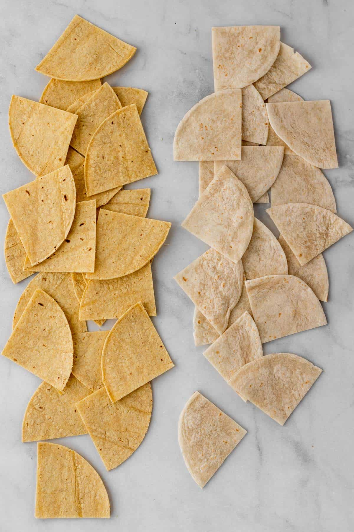 Flour and corn tortillas cut into triangles and lined up on a white background.