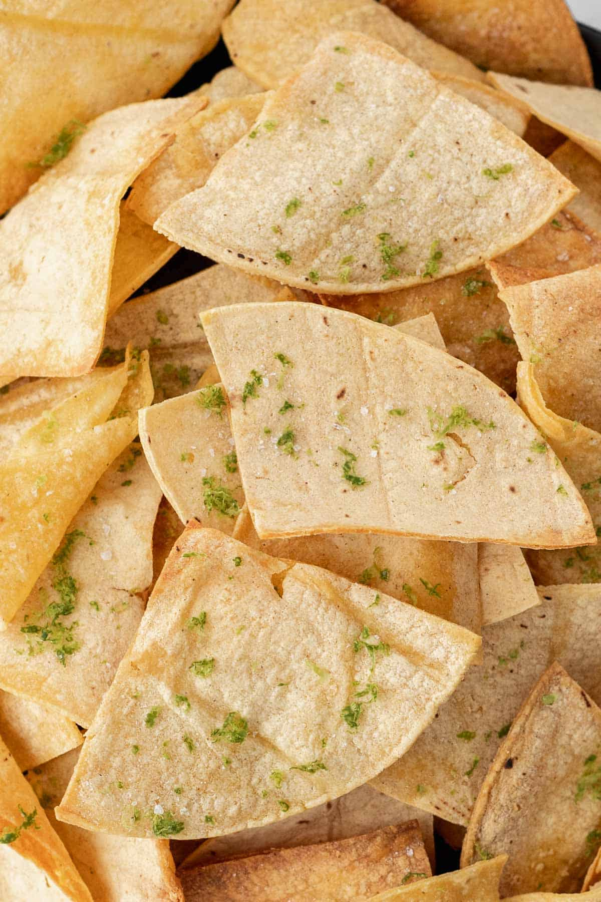 Closeup of air fryer tortilla chips seasoned with sea salt and lime zest.