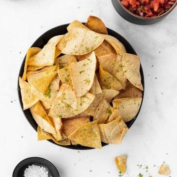 Air fryer tortilla chips in a black bowl with a chip dipped in a bowl of salsa, sea salt, and limes around it.