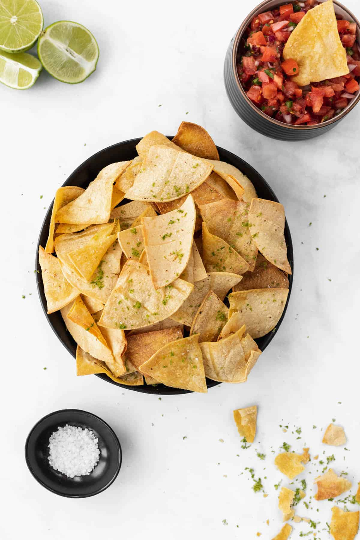 Air fryer tortilla chips in a black bowl with sea salt, limes, and a chip dipped in a bowl of salsa around it.