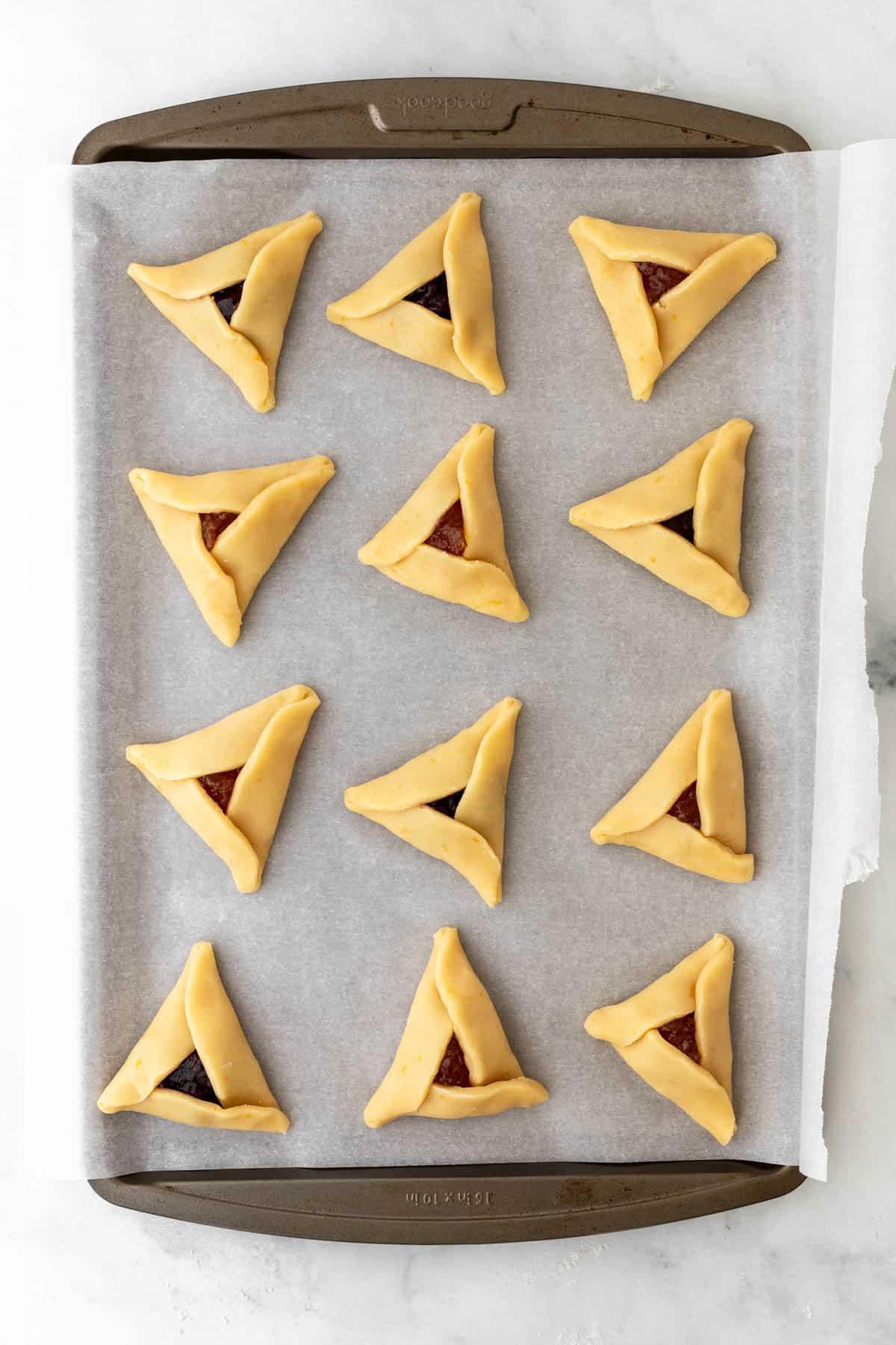 Raw hamantaschen on a cookie sheet.
