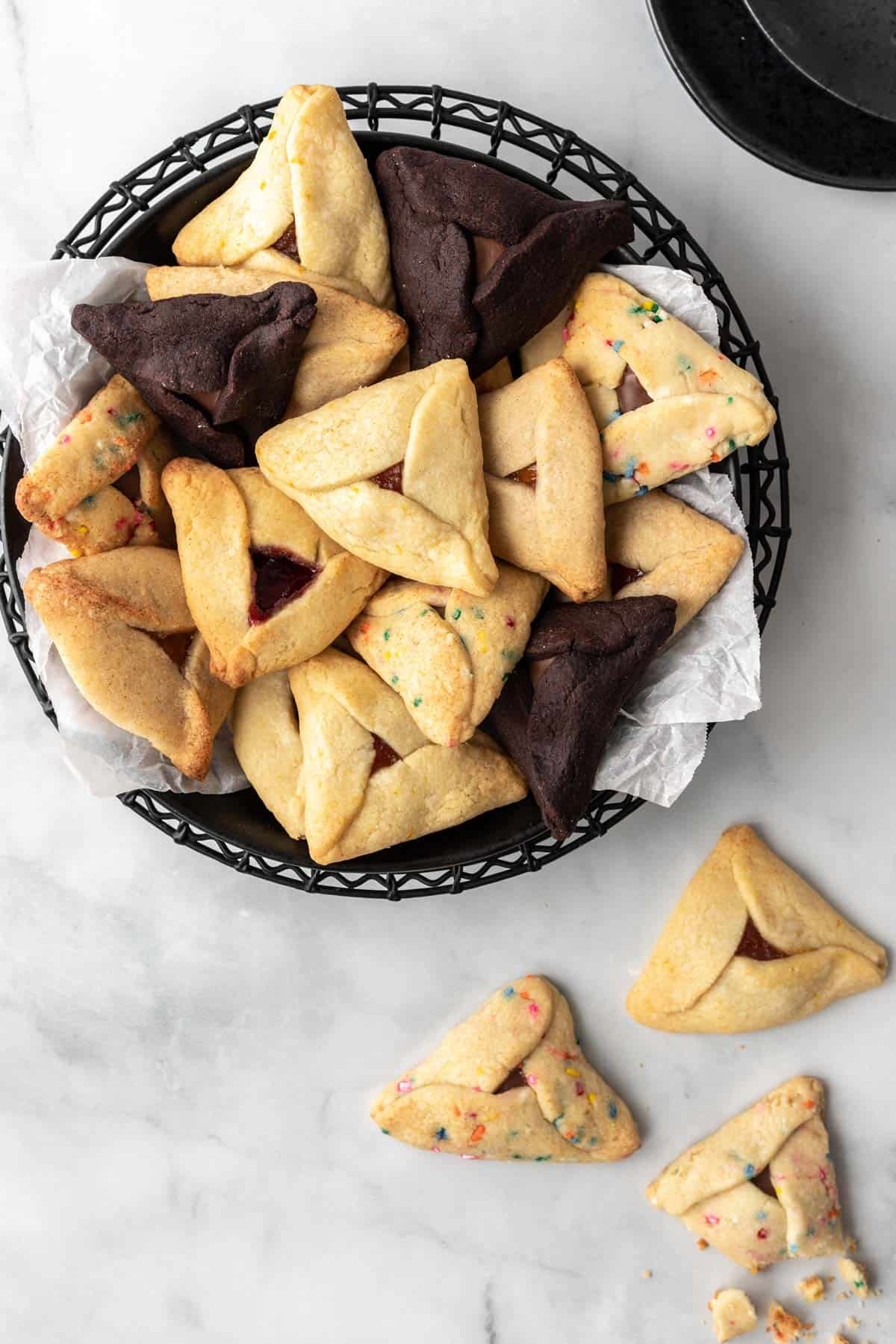 A variety of hamantaschen piled in a black bowl with 3 below it.