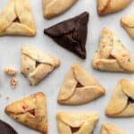 Different kinds of hamantaschen scattered on a white surface with some crumbs.