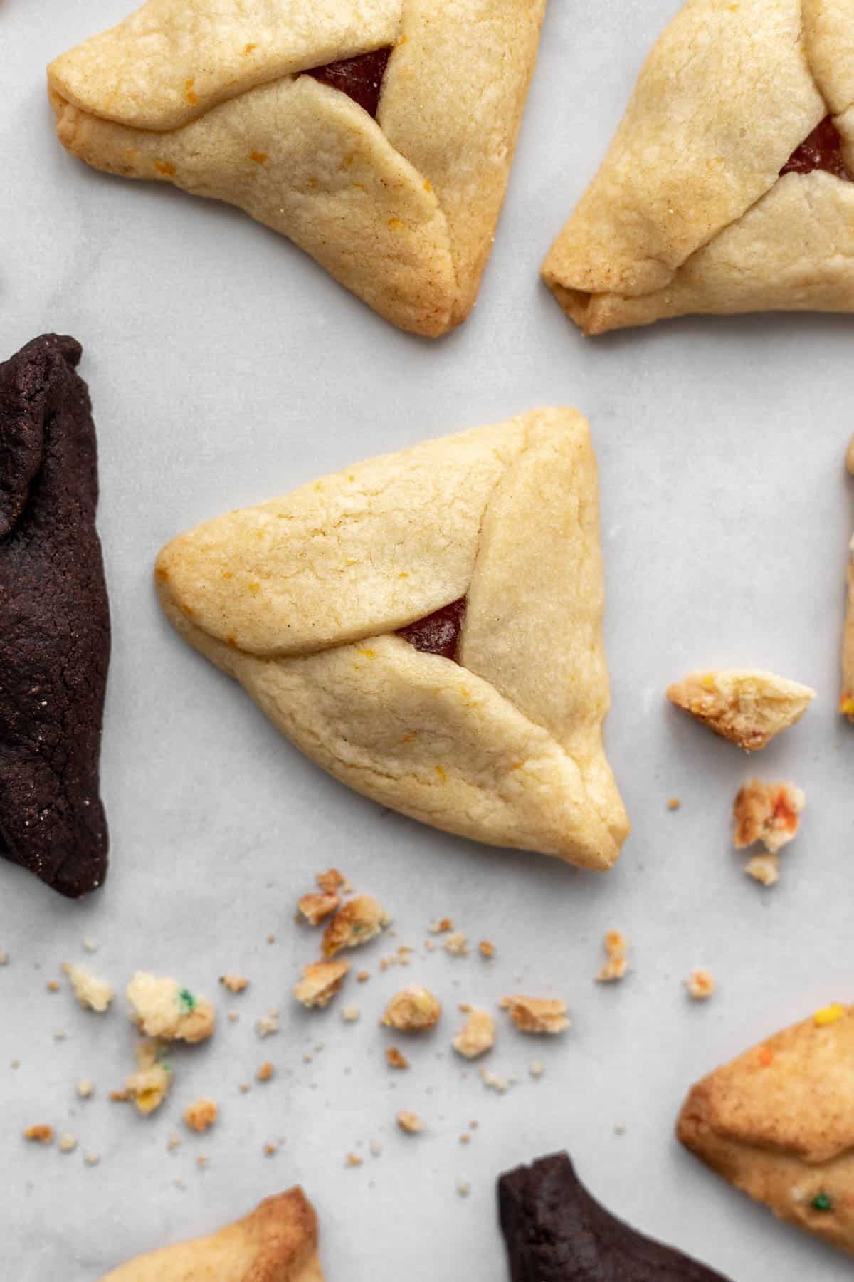 An orange marmalade hamantaschen surrounded by chocolate peanut butter and cinnamon apple hamantaschen.