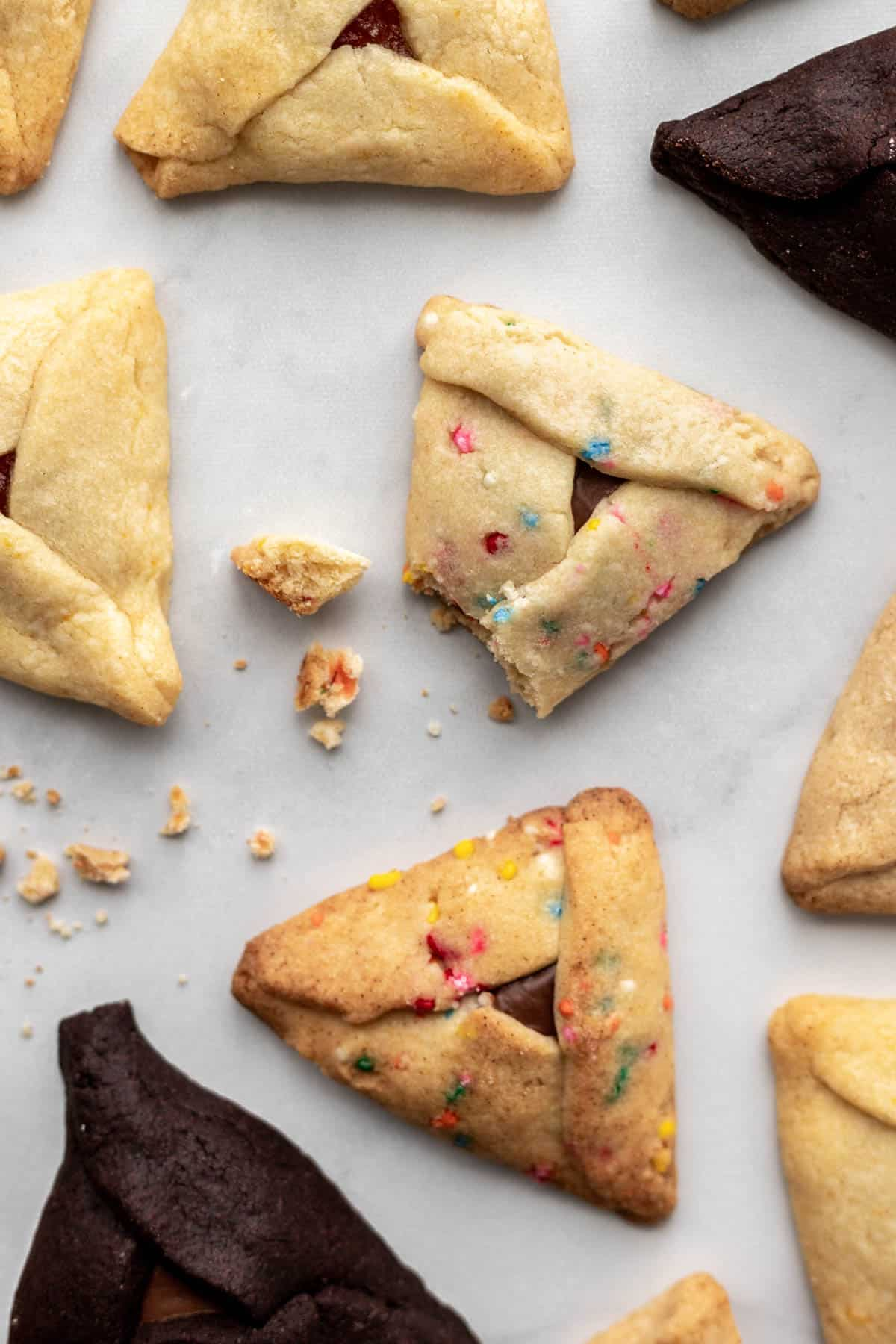 Easy hamantaschen scattered on a white surface with some crumbs.