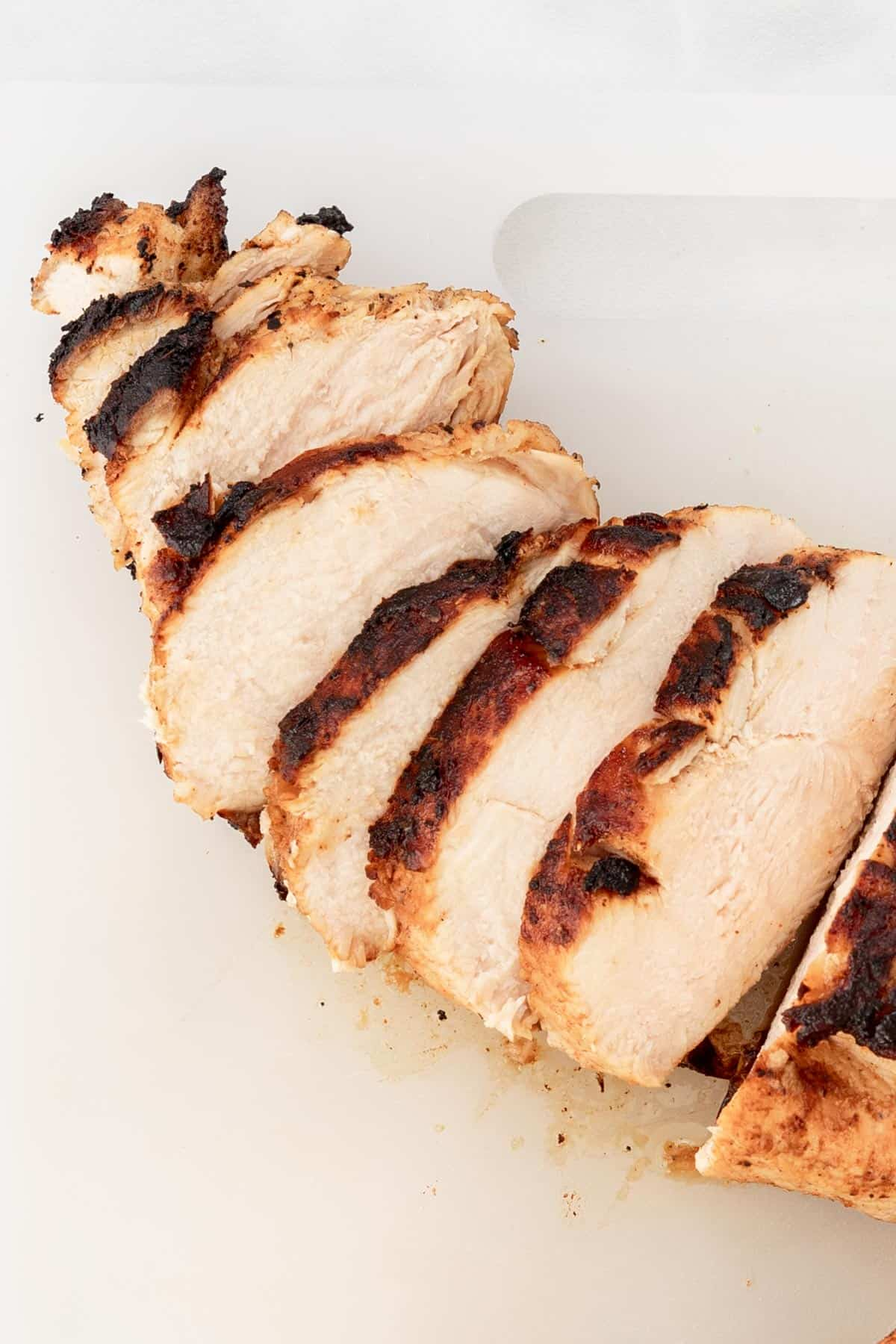 Sliced, cooked chicken breast on a white cutting board.