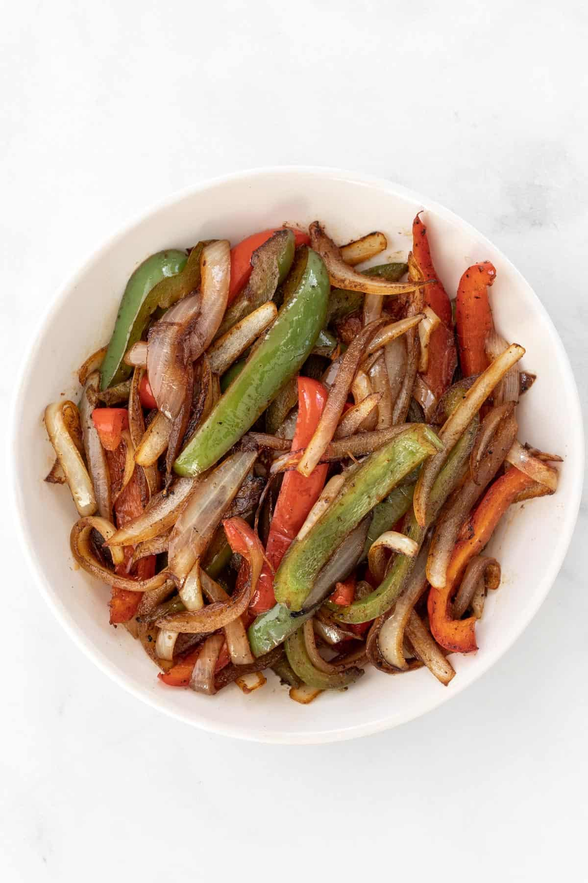 Cooked, seasoned peppers and onions in a white bowl.