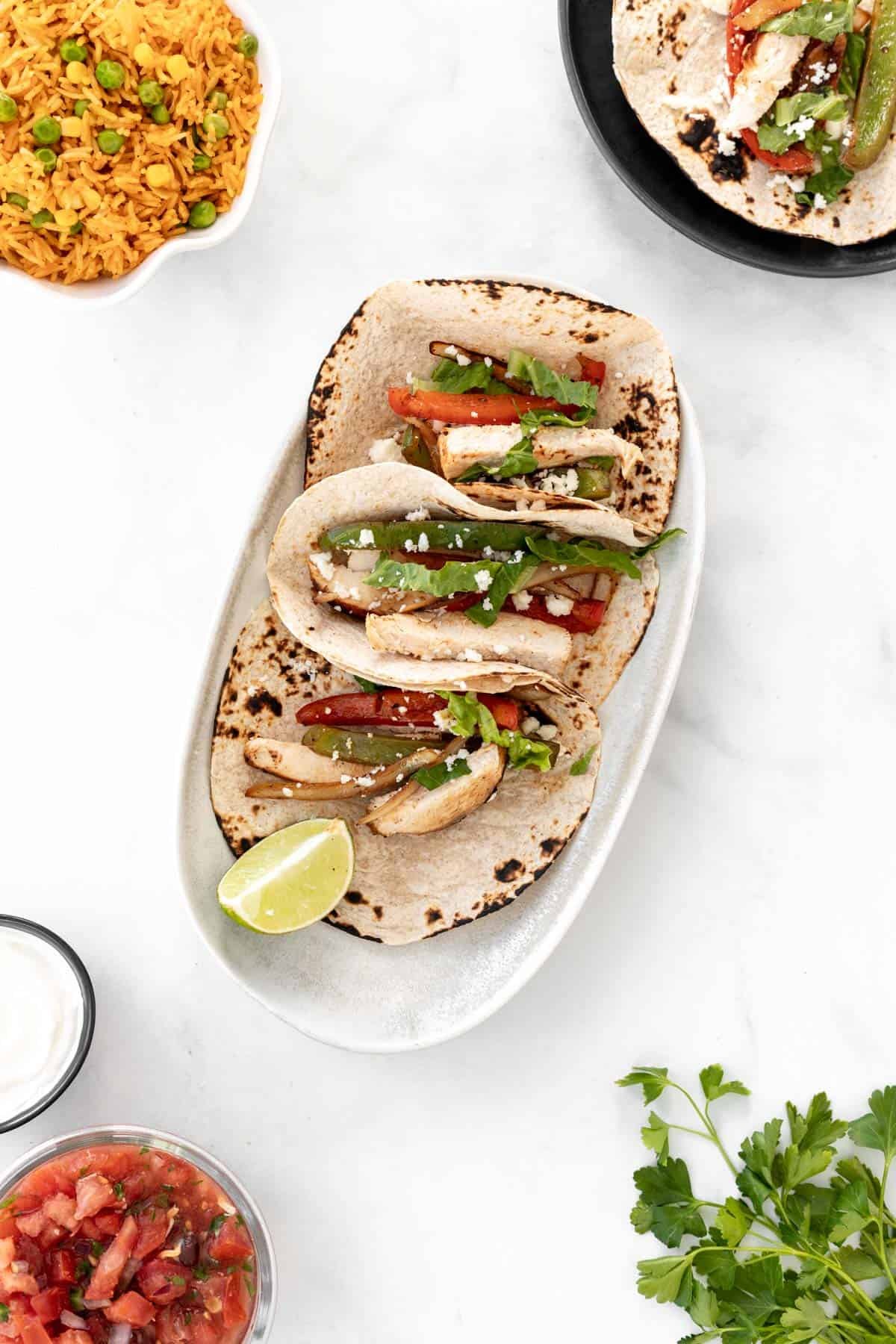 3 fajita tacos on a serving platter surrounded by another taco on a separate plate, a bunch of cilantro, and bowls of salsa, sour cream, and spanish rice.