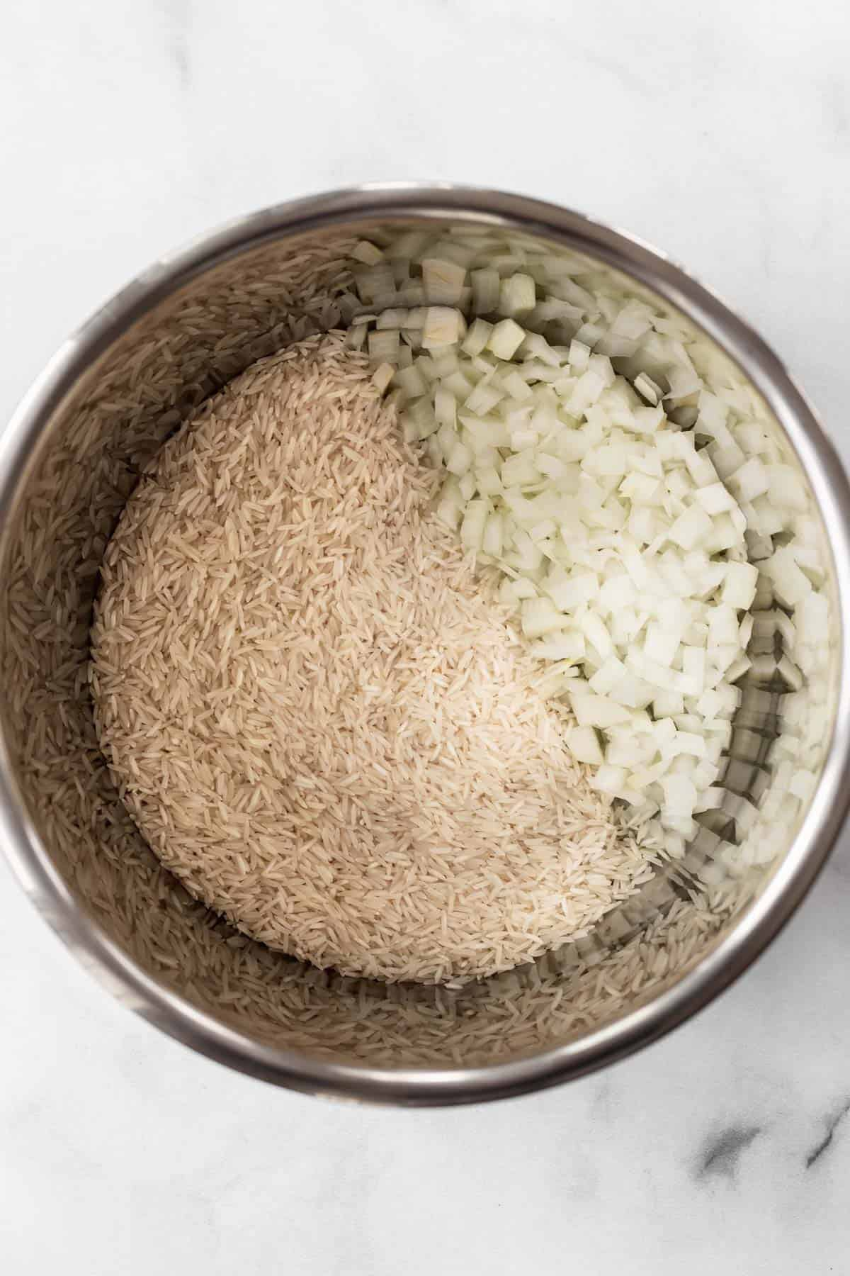 Chopped onions and basmati rice in an instant pot.
