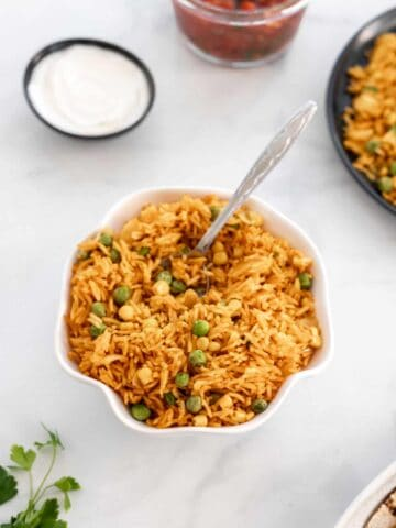 Instant pot Spanish rice in a white ruffled bowl surrounded by cilantro and small bowl of sour cream.