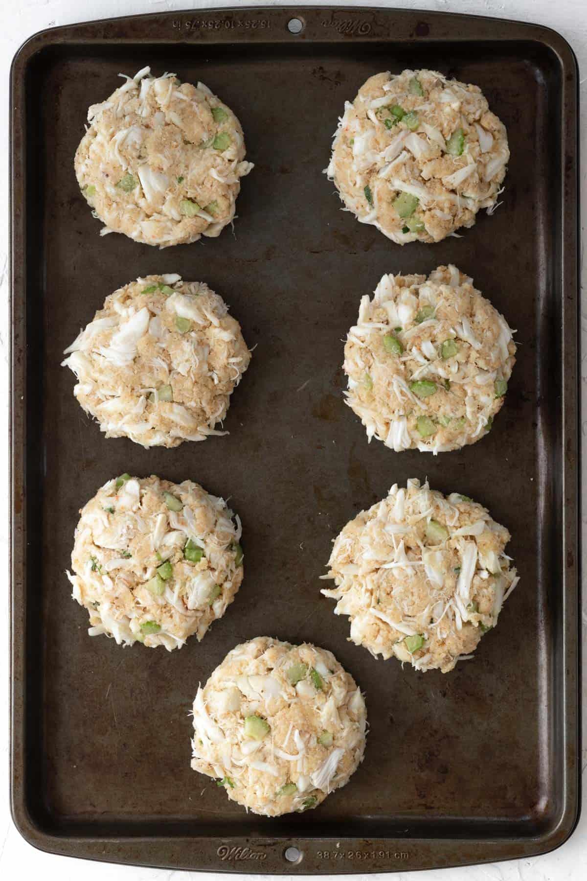 7 raw crab cakes on a metal baking sheet.