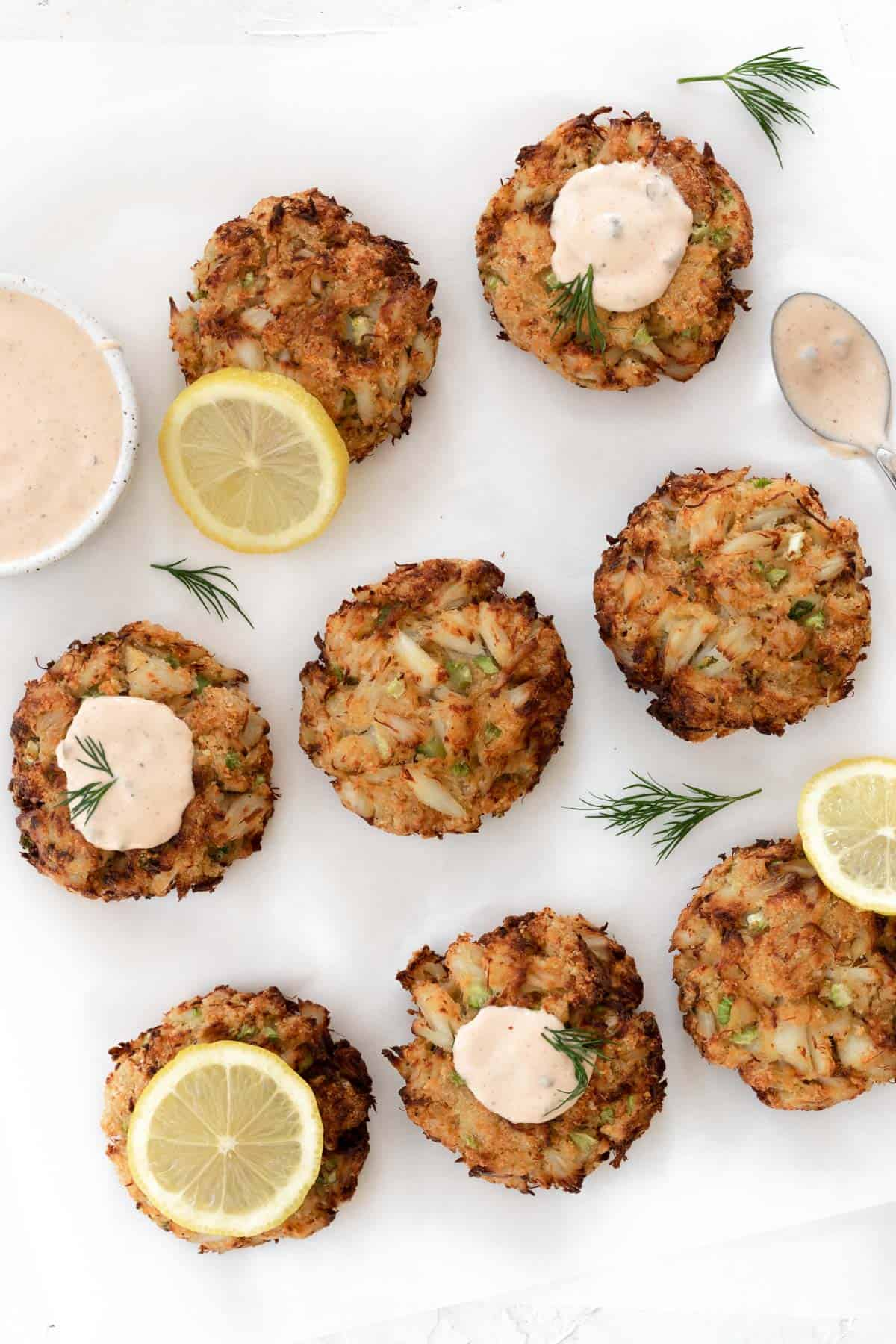 Air fryer crab cakes on a white backdrop with a bowl of remoulade sauce, lemon slices, and dill sprigs around them.