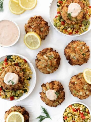 Air fryer crab cakes served with corn succotash, remoulade sauce, lemon slices, and fresh dill.