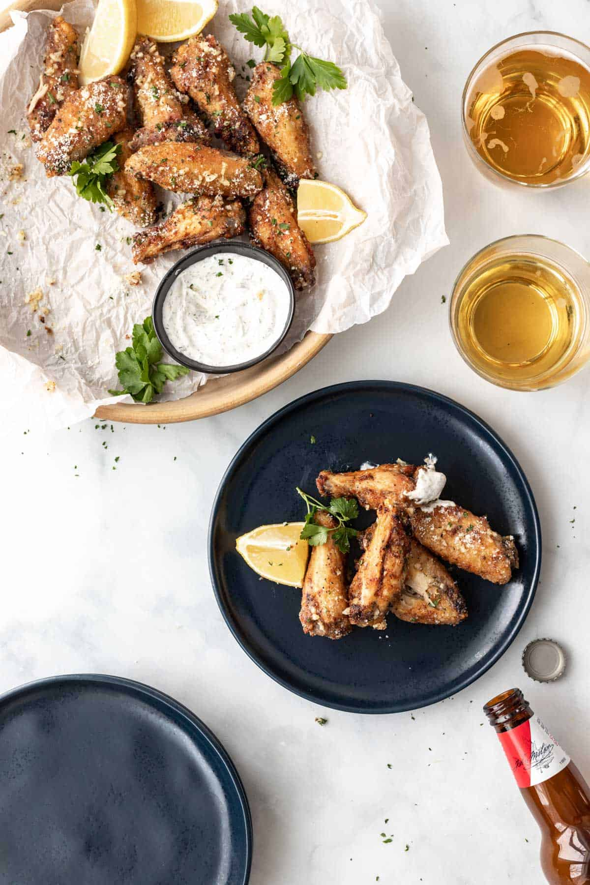 Chicken wings on a blue plate surrounded by a serving dish full of wings, 2 cups of beer, an empty beer bottle, and a bottle cap.