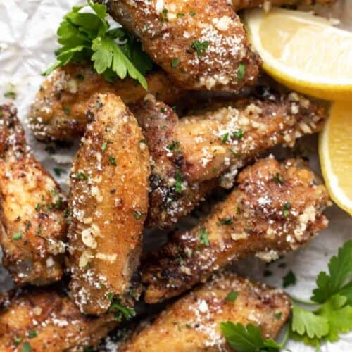 A closeup of air fryer chicken wings topped with parmesan cheese and parsley.