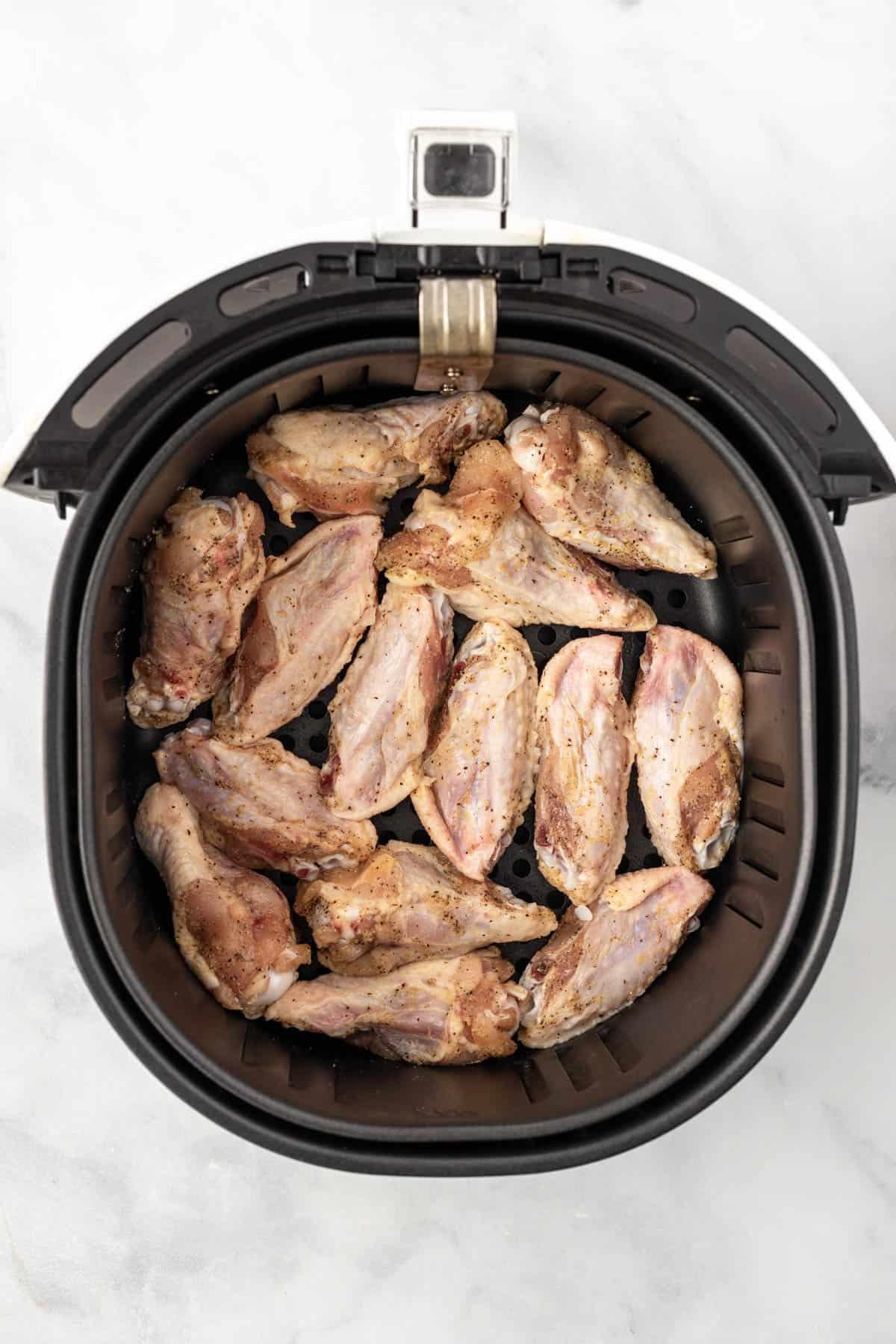 Raw, seasoned chicken wings in an air fryer basket.