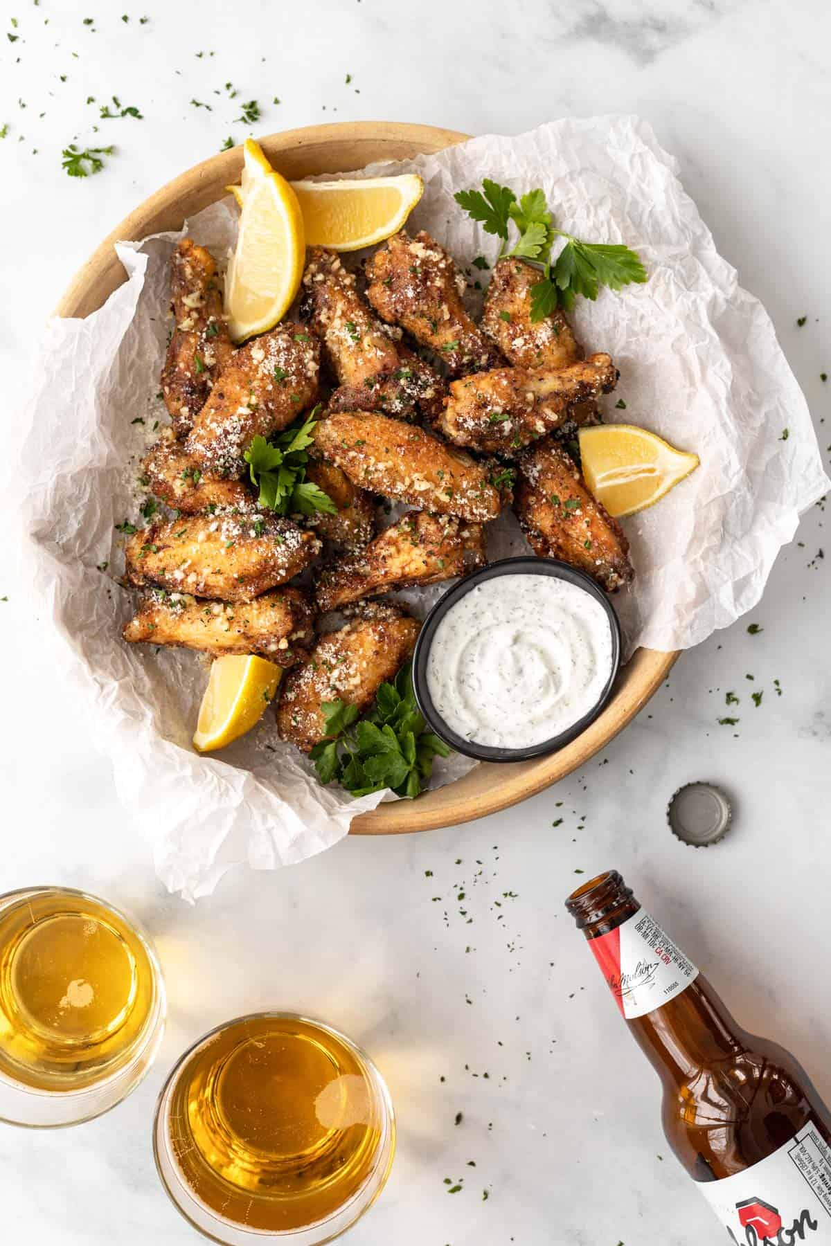 Air fryer parmesan garlic wings piled into a serving dish with a side of ranch, 2 glasses of beer, a beer bottle, and a bottle cap.
